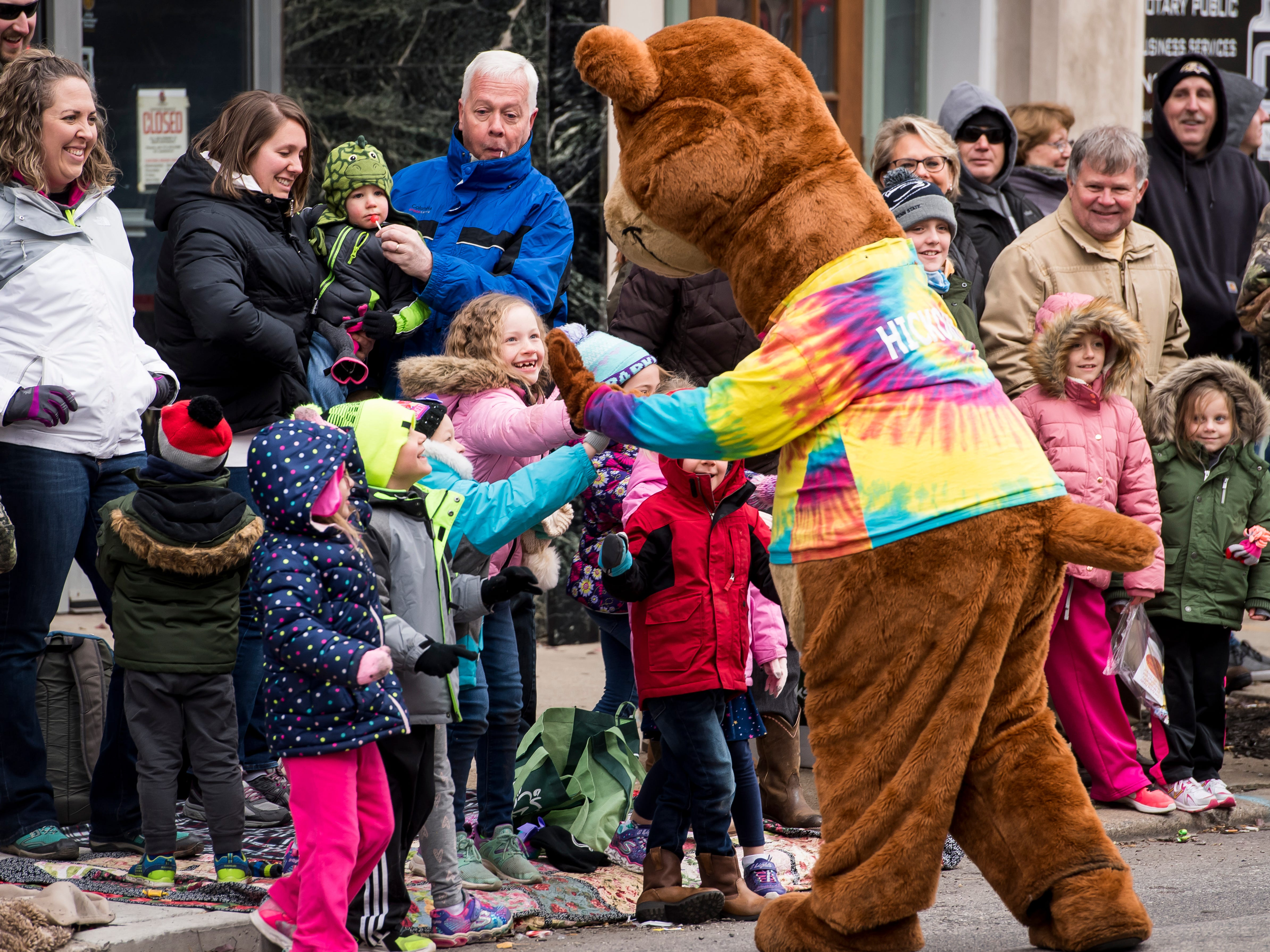 The Hickory Falls mascot doles out high-fives during the annual Hanover Christmas parade on Friday, November, 23, 2018.