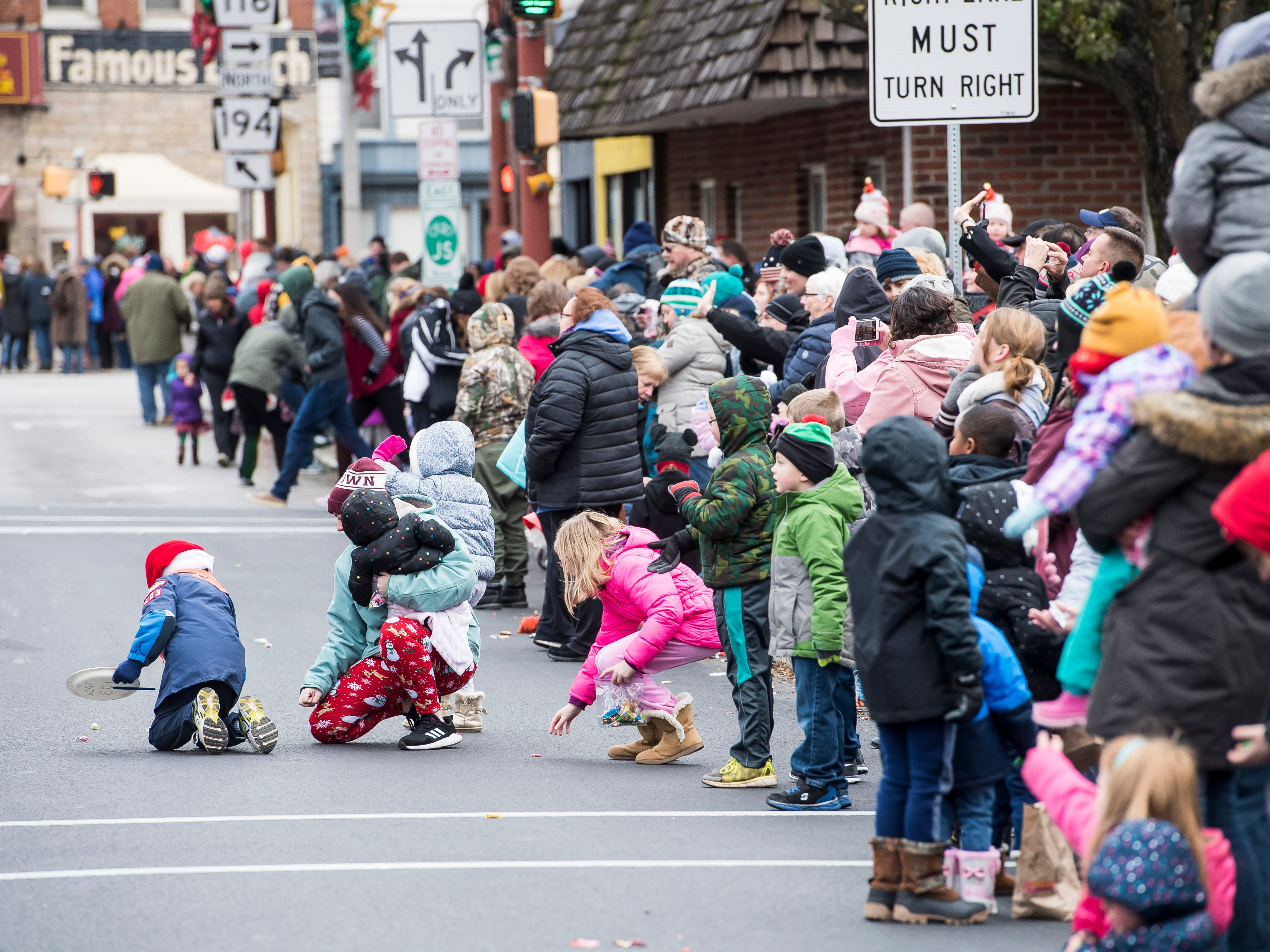 Children gather candy during the annual Hanover Christmas parade on Friday, November, 23, 2018.