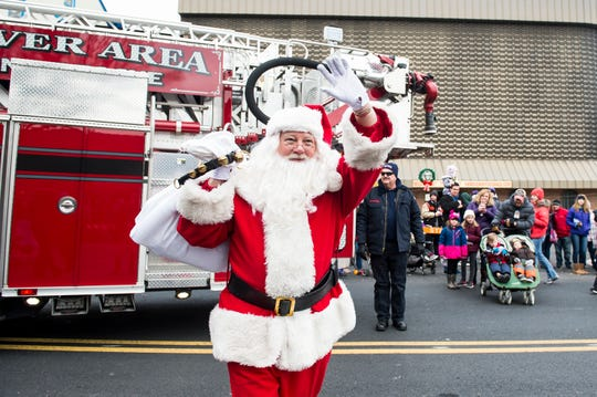 Santa waves to the crowd after arriving at his brand new cabin in the Hanover Square on Friday, November, 23, 2018.