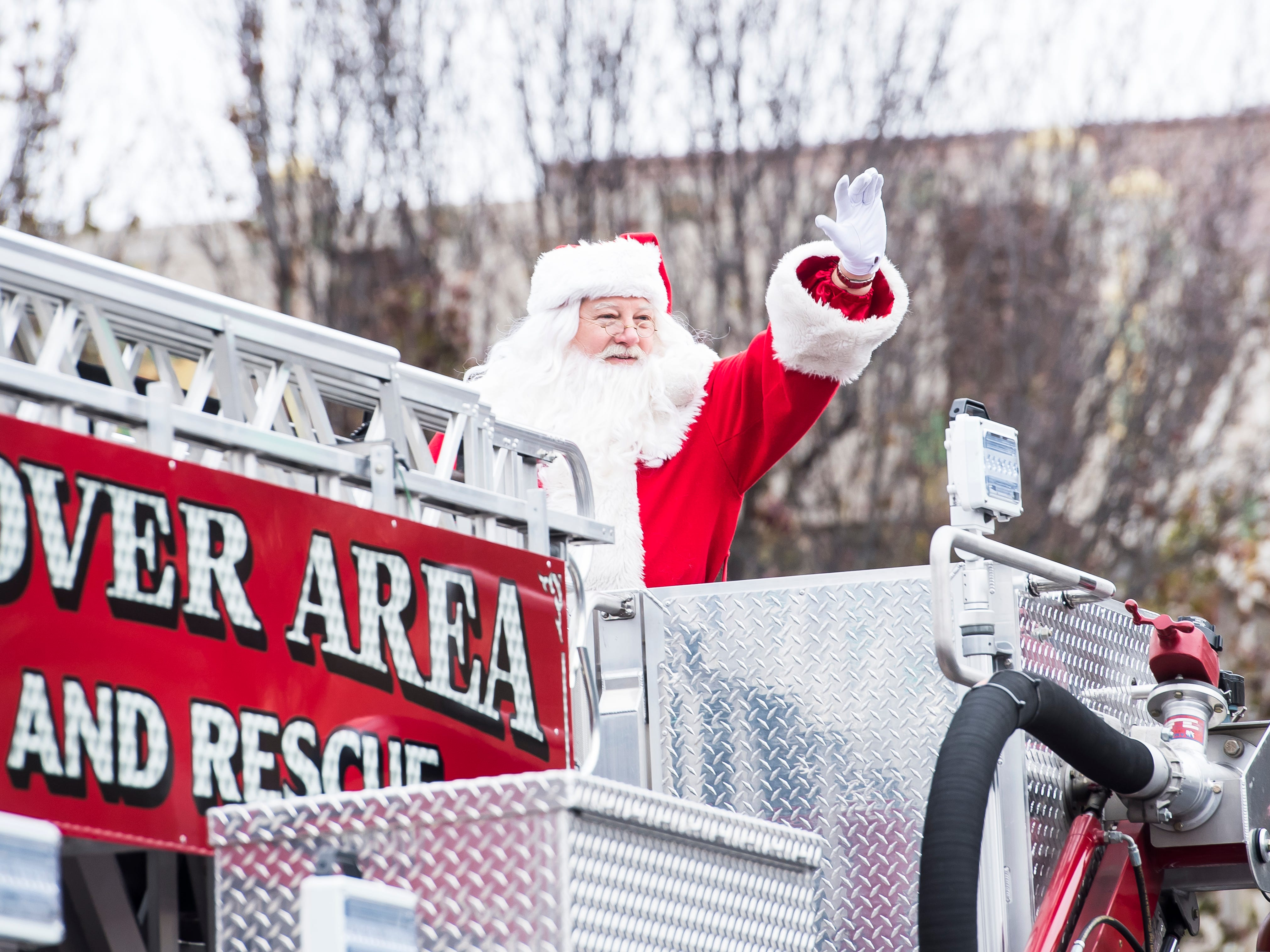 Santa waves to the crowd while riding in the bucket of a Hanover Area Fire and Rescue ladder truck in the Hanover Christmas parade on Friday, November, 23, 2018.