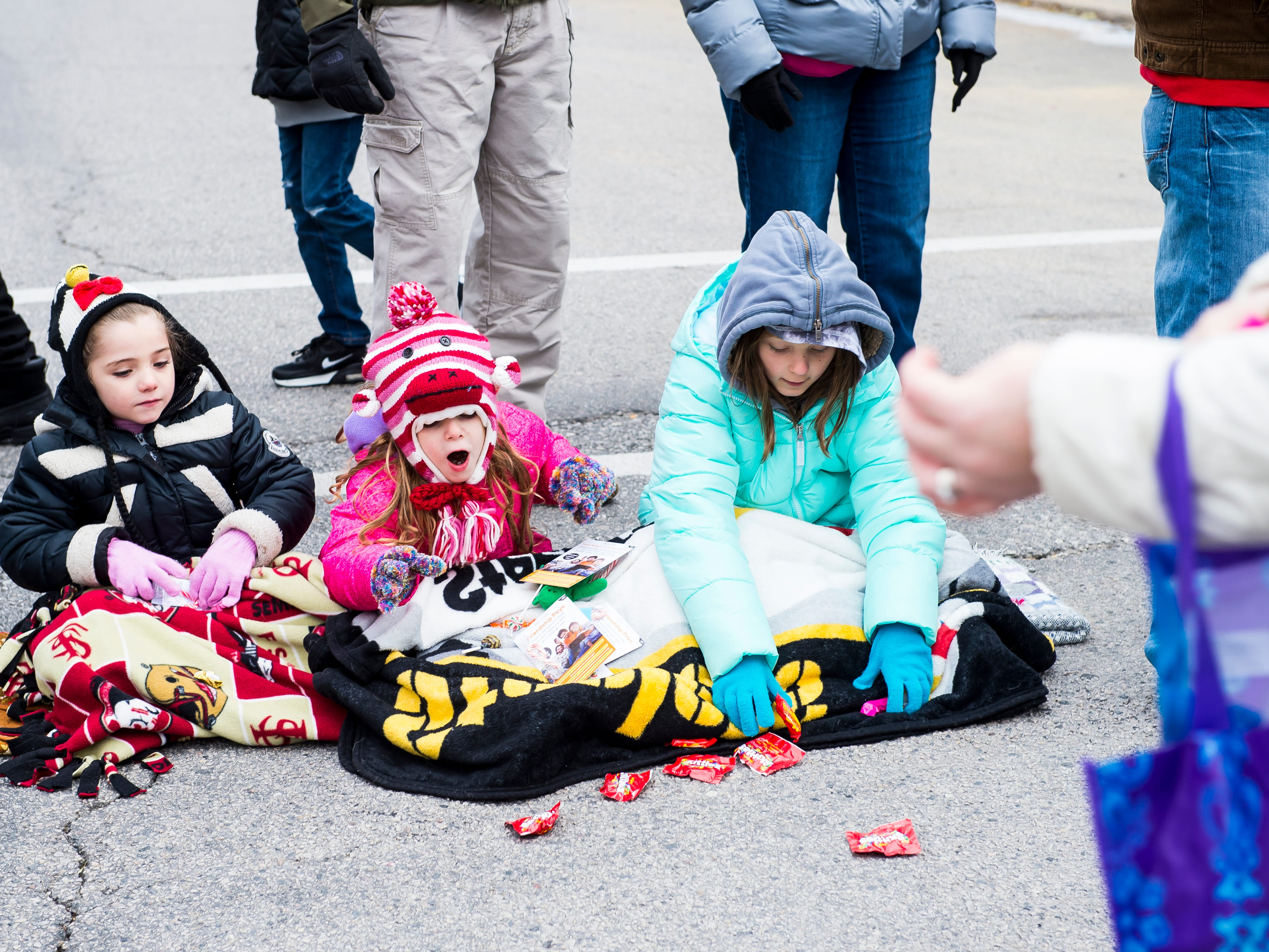 Children collect candy off the ground during the annual Hanover Christmas parade on Friday, November, 23, 2018.