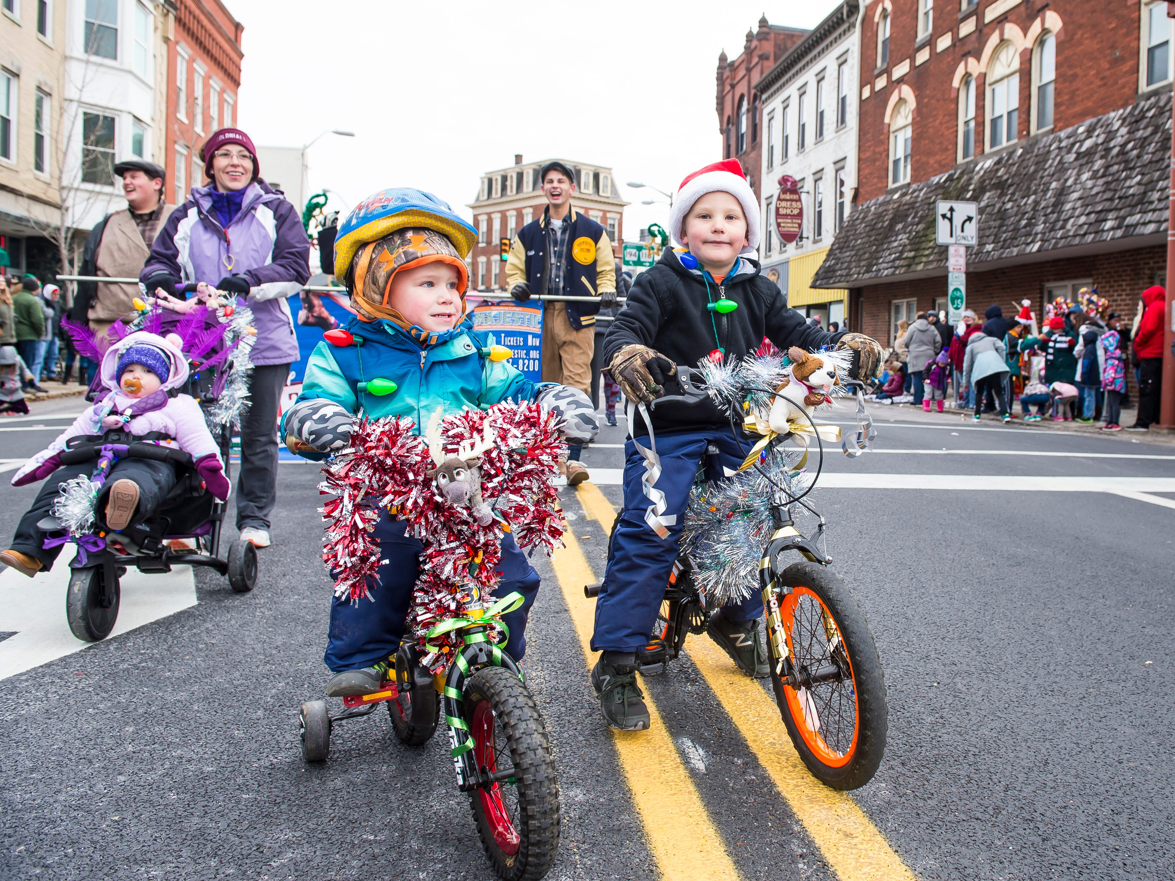 Children ride bicycles in the annual Hanover Christmas parade on Friday, November, 23, 2018.