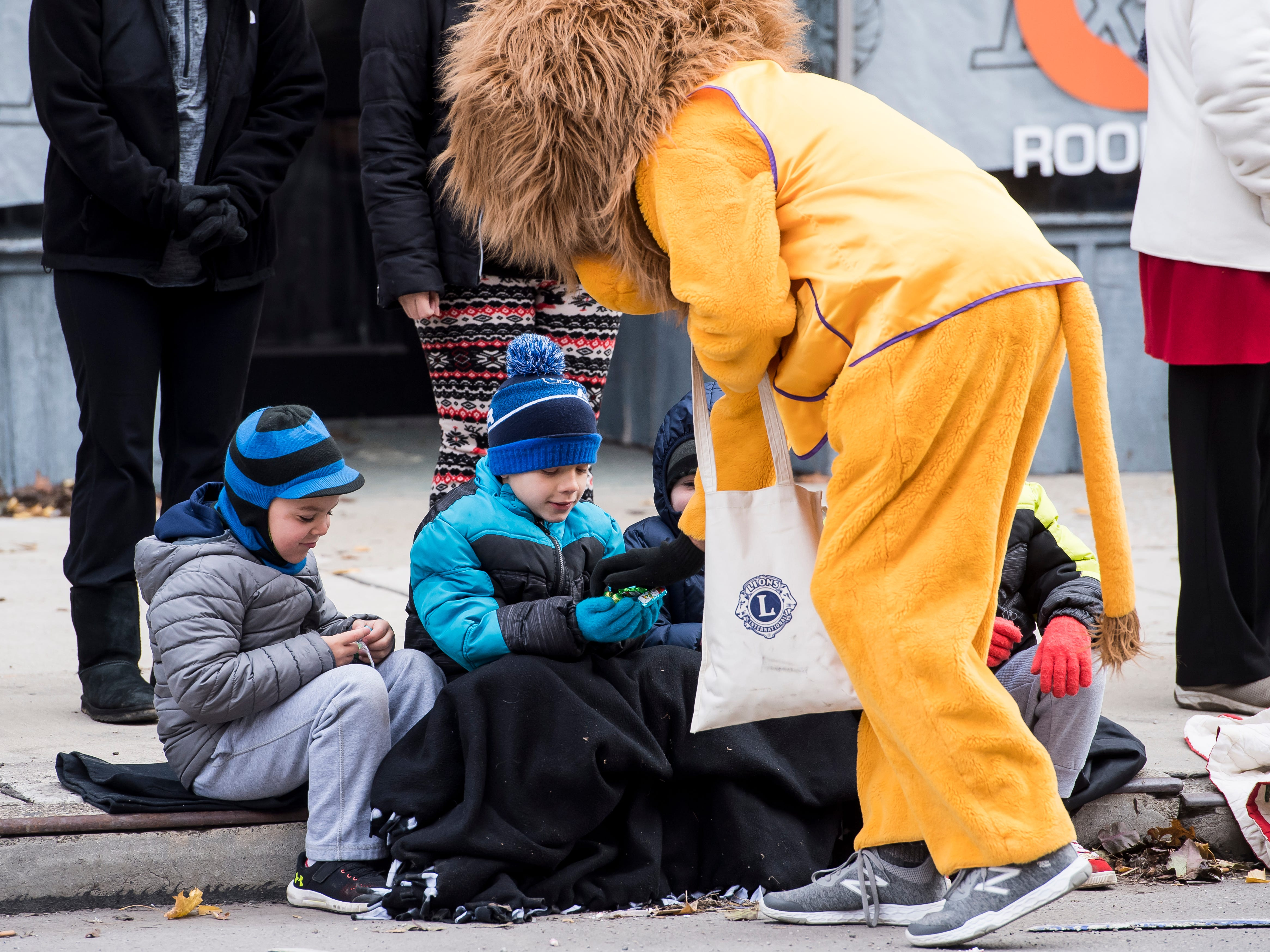 The Hanover Lions Club mascot hands out candy to children during the annual Hanover Christmas parade on Friday, November, 23, 2018.