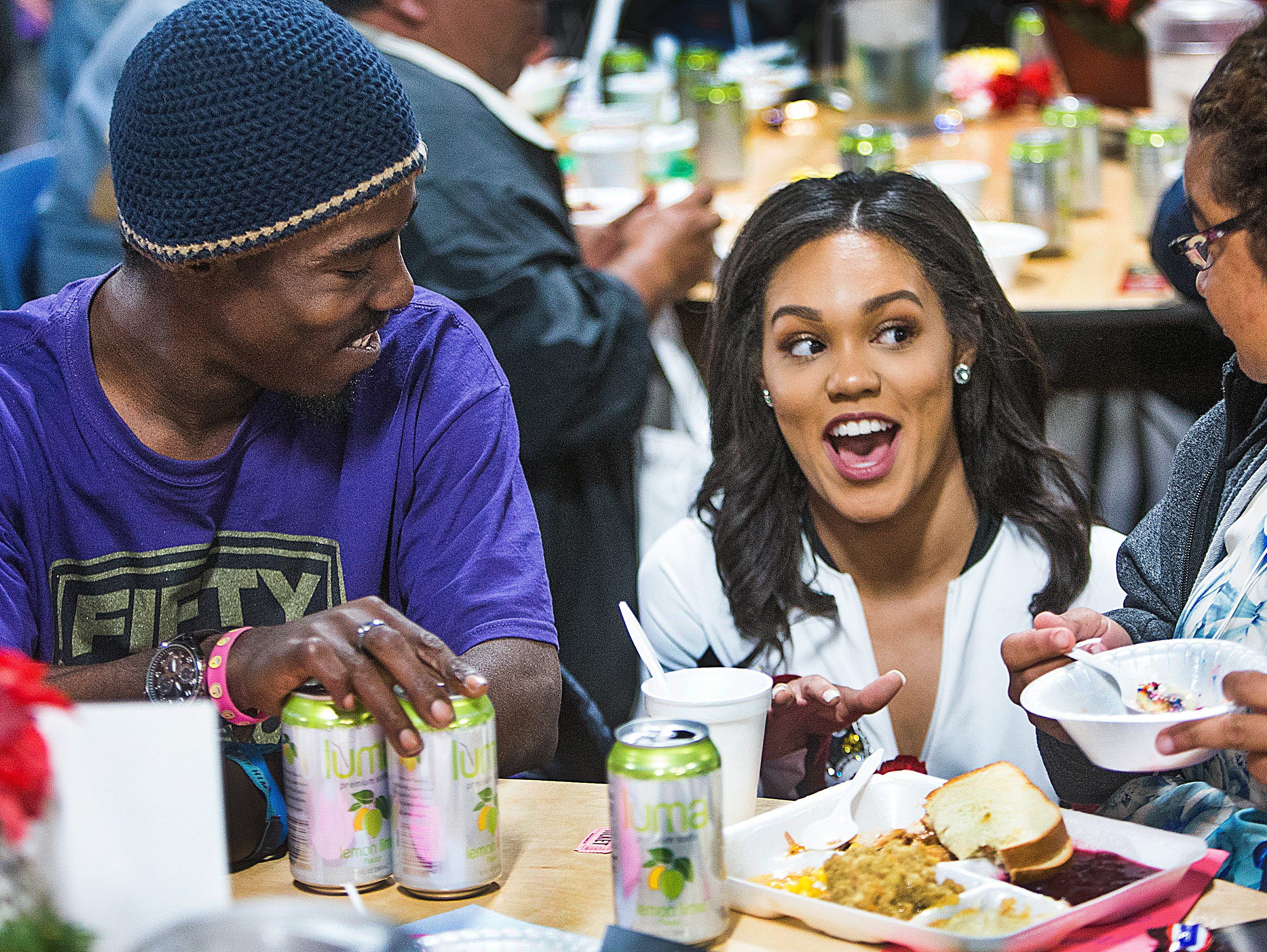 Arizona Cardinals cheerleader Stephanie Hardy, middle, speaks with Sandorian Steele, left, and Jessica Rodriguez, right, at the Thanksgiving Day meal served by volunteers for the St. Vincent de Paul Society. Hundreds enjoyed turkey, mashed pototaoes and pumpkin pie at the Human Services Campus Dining Room in Phoenix, Thursday, November 22, 2018.