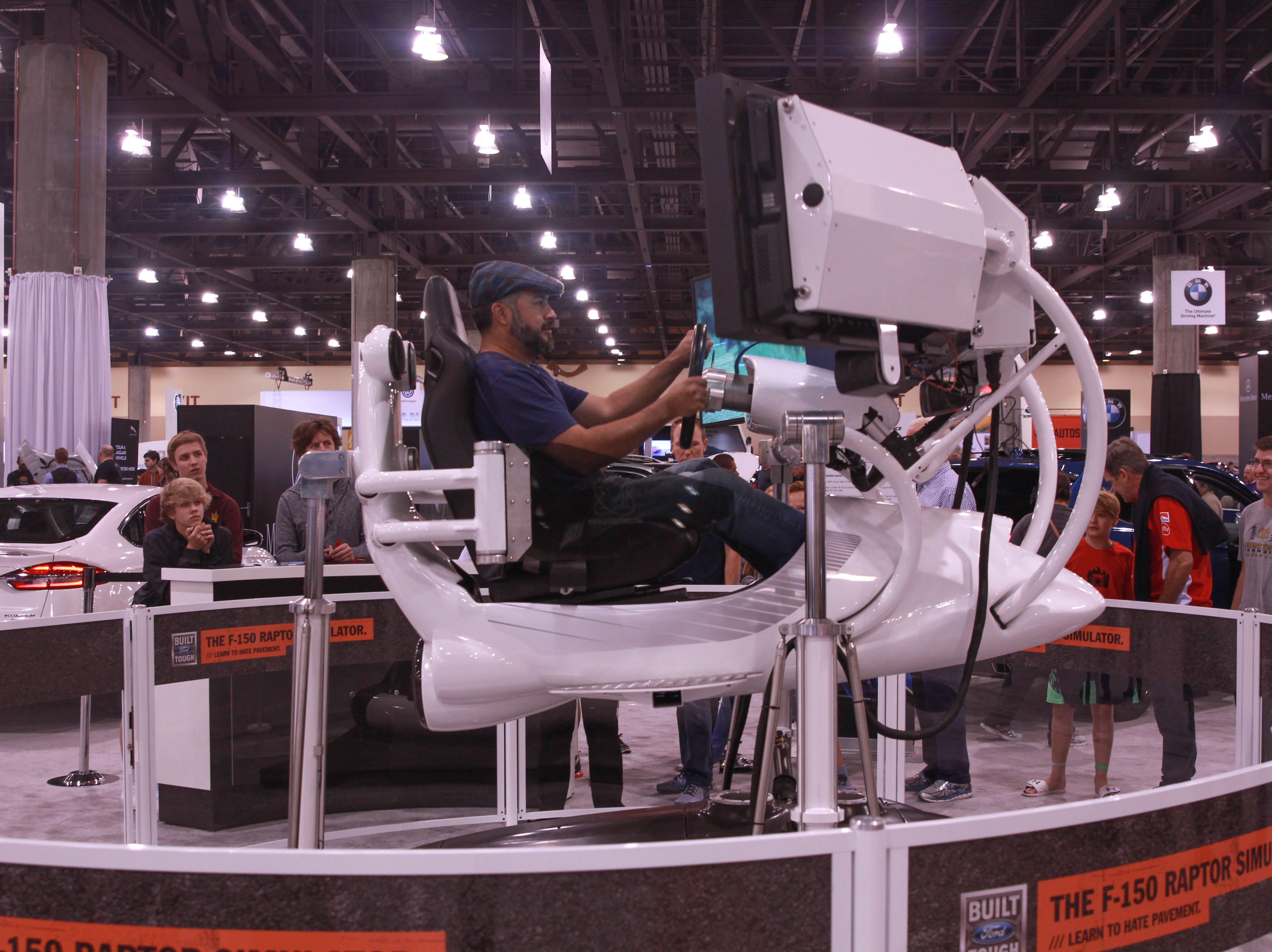 Yuri Robles tries a Ford F-150 Raptor simulator at the Arizona International Auto Show, Nov., 23, 2018.