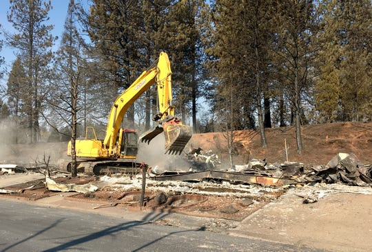 An excavator pulls away a metal roof from a burned-out mobile home in Paradise, California, on Nov. 20, 2018. The Ridgewood Mobile Home Park was destroyed by the Camp Fire.