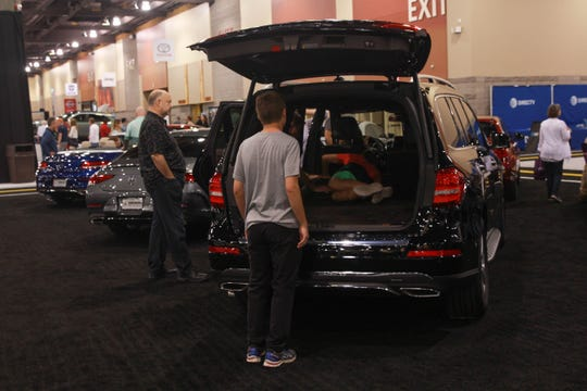 Visitors at the Arizona International Auto Show can compare vehicles side by side for trunk space and other features.