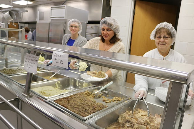 Volunteers at the 10th annual Community Thanksgiving Dinner at Woodmore High School serve up hundreds of meals on Thursday.