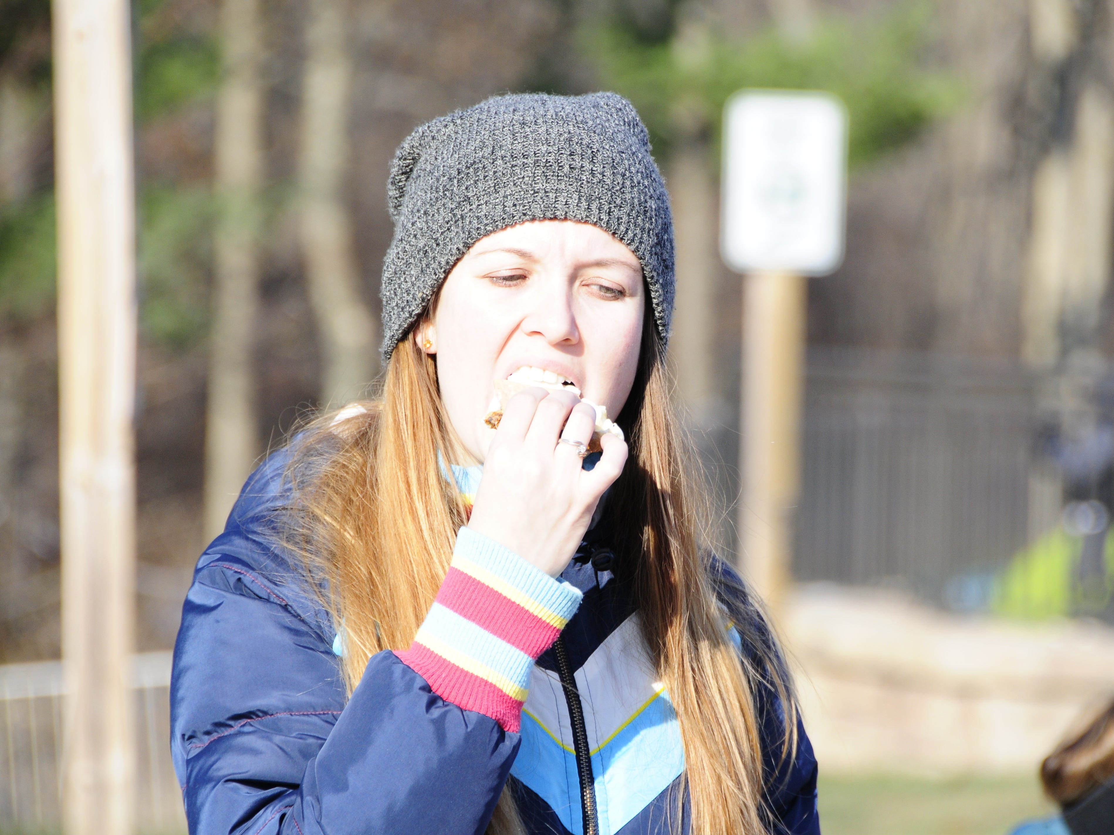 Breanna Thornton bites into a s'more at Friday's Opt Outside hike at Columbus County Park.