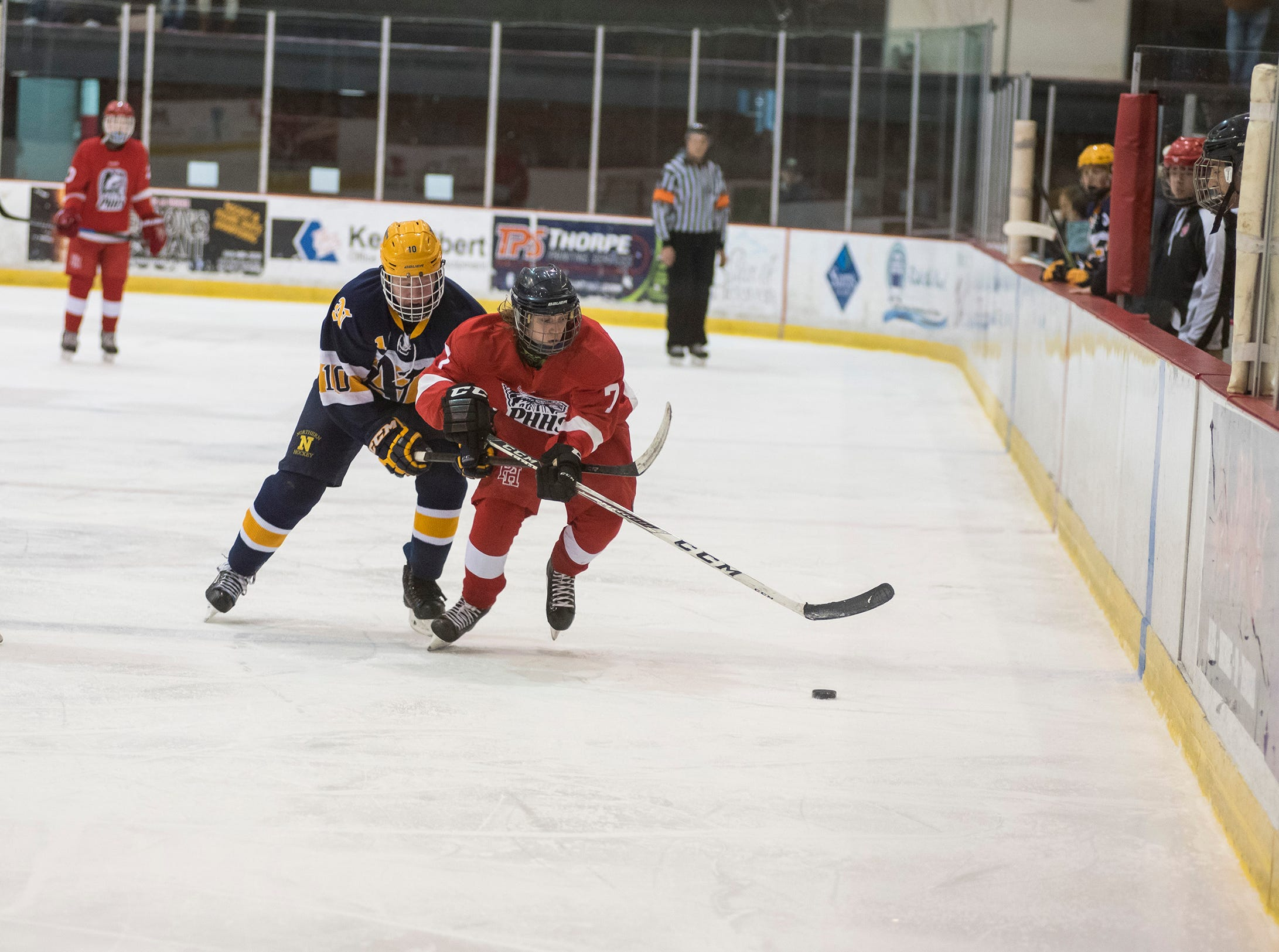 Port Huron High School forward Matthew Fleming (7) and Port Huron Northern High School forward Brendan Dickinson race to the puck during the Larry Manz Holiday Hockey Tournament Friday, Nov. 23, 2018 at McMorran Arena.