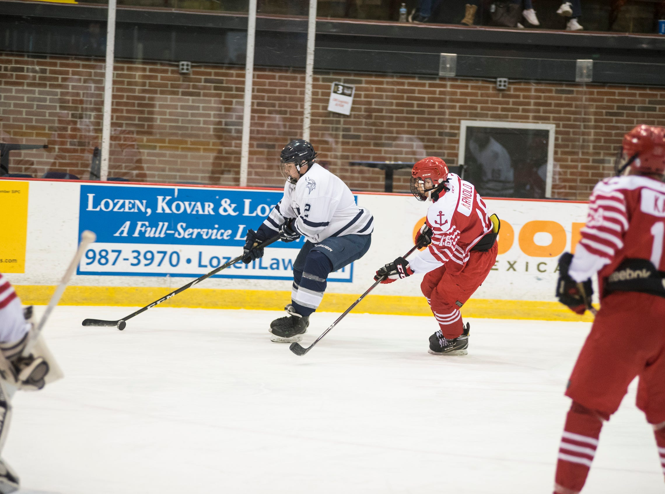 Anchor Bay High School defense Payen Arnold (right) chases Marysville High School defense Brendan Nunez as he skates with the puck during the Larry Manz Holiday Hockey Tournament Friday, Nov. 23, 2018 at McMorran Arena.