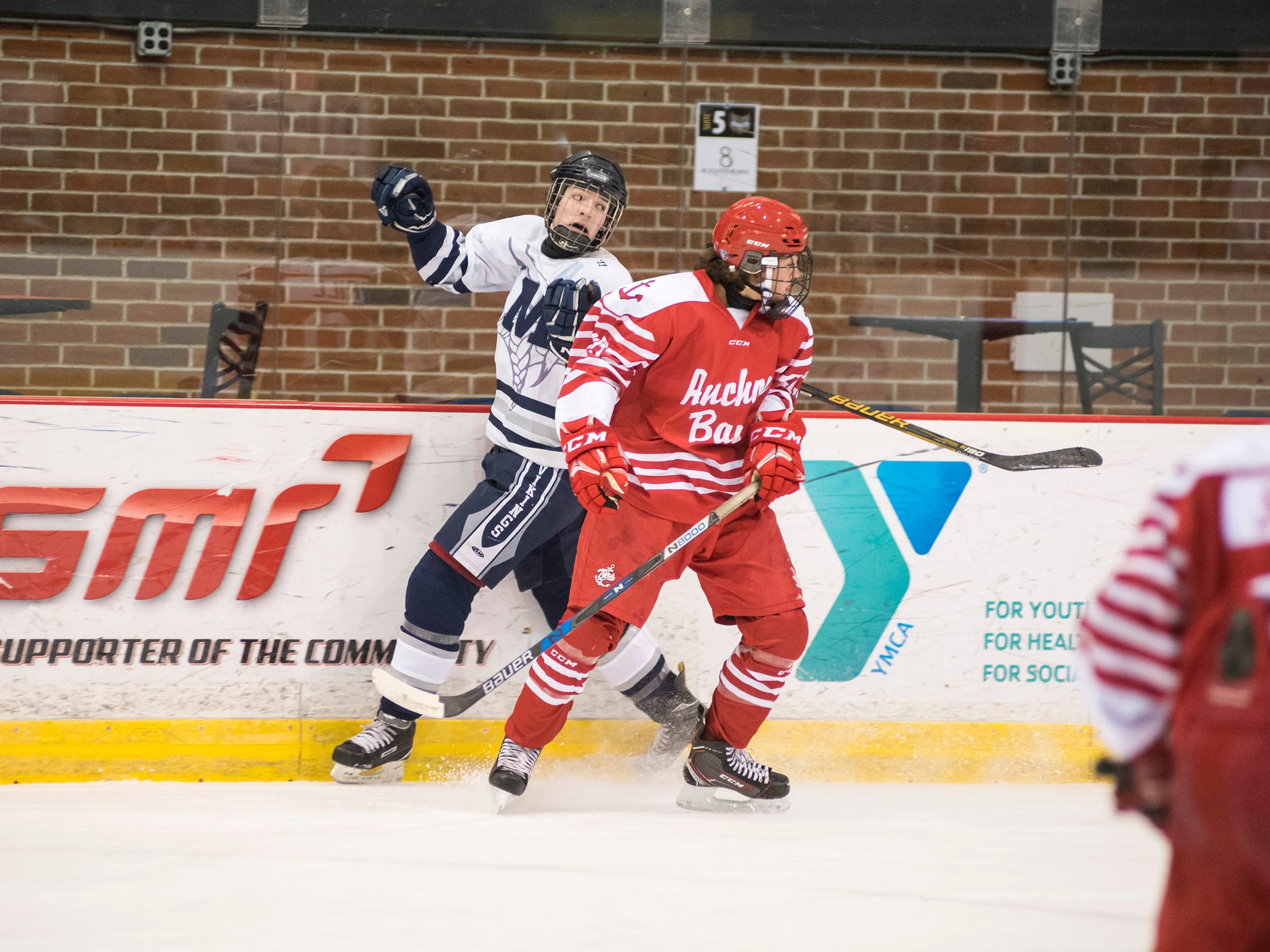 Anchor Bay High School defense James Skorupski (right) holds Marysville High School forward Hunter Miller against the wall during the Larry Manz Holiday Hockey Tournament Friday, Nov. 23, 2018 at McMorran Arena.