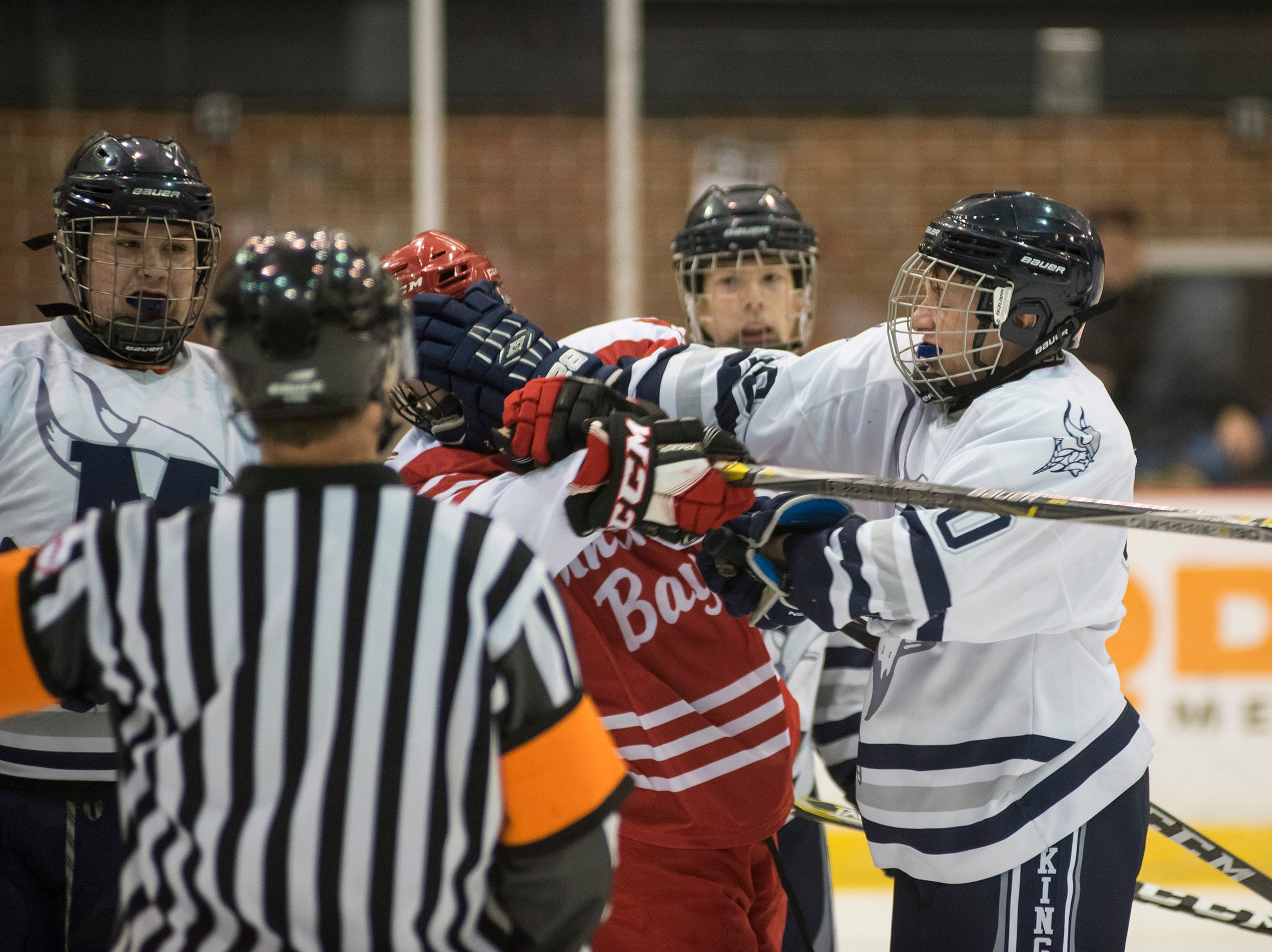 Marysville High School defense Hunter Glynn (right) reaches for an Anchor Bay player's facemask during the Larry Manz Holiday Hockey Tournament Friday, Nov. 23, 2018 at McMorran Arena.