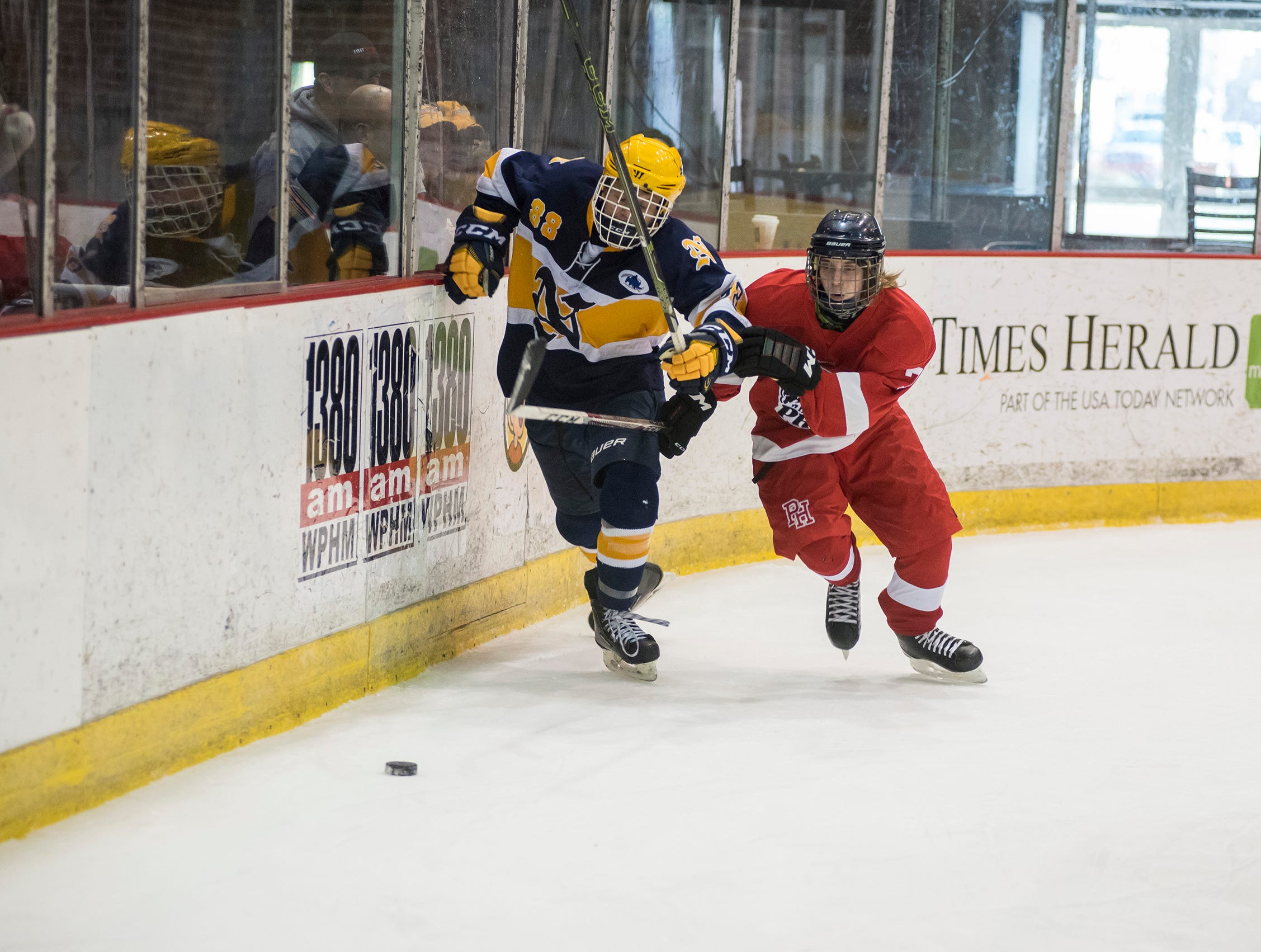 Port Huron Northern High School forward Dominic Ruiz (88) and Port Huron High School forward Mason Powell race for the puck during the Larry Manz Holiday Hockey Tournament Friday, Nov. 23, 2018 at McMorran Arena.