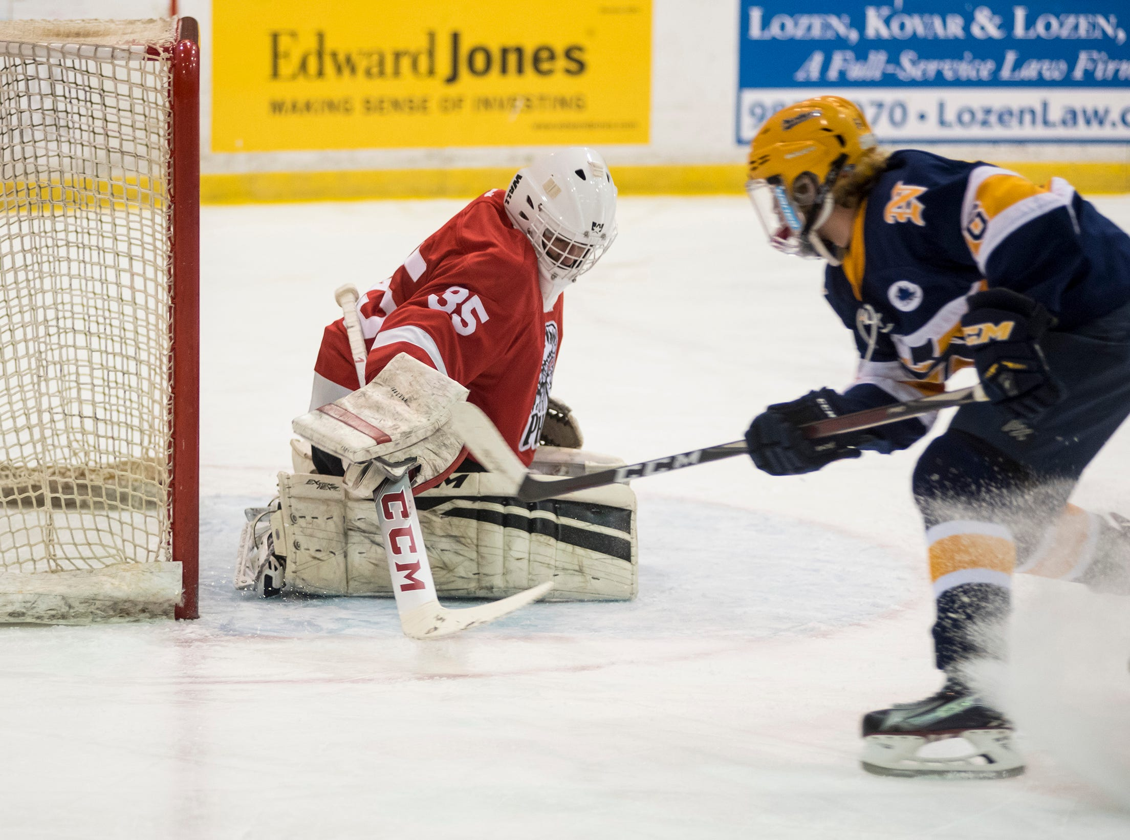 Port Huron High School goalie Josh Witer (35) tries to block a shot by Port Huron Northern High School forward Cole Peyerk during the Larry Manz Holiday Hockey Tournament Friday, Nov. 23, 2018 at McMorran Arena.
