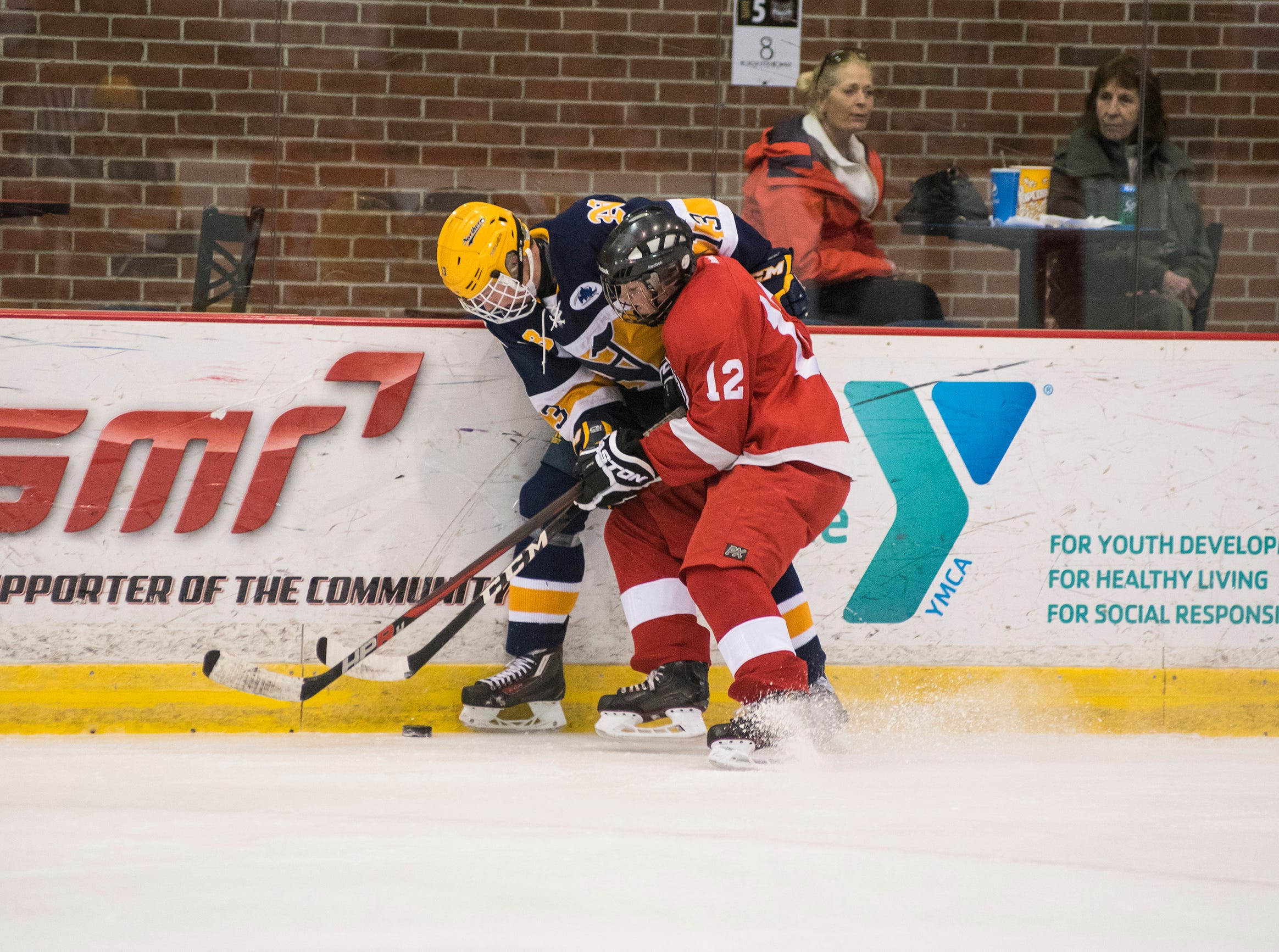 Port Huron High School forward Matthew Fleming (12) hold Port Huron Northern High School forward Nick Platzer against the wall while they fight for the puck during the Larry Manz Holiday Hockey Tournament Friday, Nov. 23, 2018 at McMorran Arena.