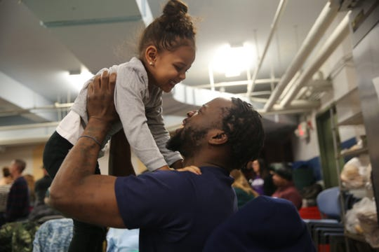 Lemitri Grant (right) lifts up his niece Nyla Grant (left) during the annual Eileen Hickey Holiday Dinner on Thanksgiving. He said he wouldn't be able to afford a Thanksgiving meal and was thankful for the event.