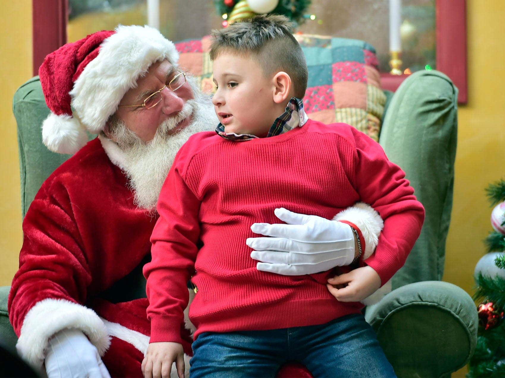 Santa listens as Noah Robinson, McConnellsburg, tells him what is on his Christmas list at Chambersburg Mall. Shoppers were at local malls and stores to search for Black Friday deals, November 23, 2018.