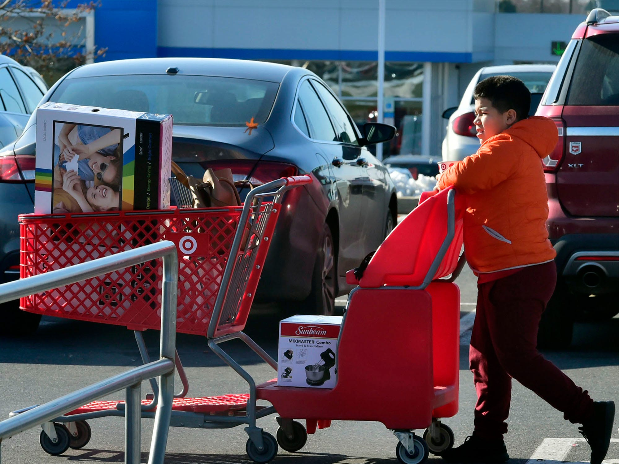 Frank Barrientos, 11, takes a cart to the car while shopping with family members at stores in Chambersburg Crossing on Friday, November 23, 2018. Shoppers were at the malls and stores looking for great deals on Black Friday.