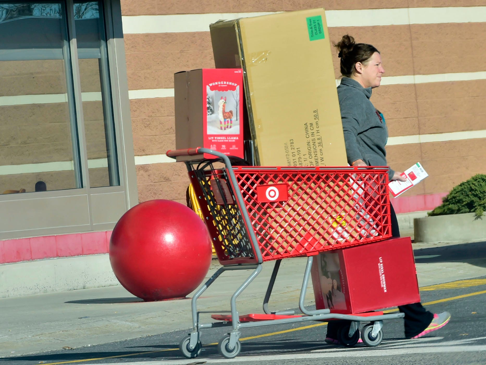 A woman pulls a cart filled with purchases from Target at Chambersburg Crossing on Friday, November 23, 2018. Shoppers were at the malls and stores looking for great deals on Black Friday.