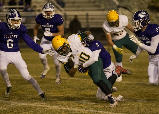 Manogue Miners running back Peyton Dixon (10) is tackled by  Spanish Springs Michael Binnell (8) on Nov 9 at Spanish Springs.