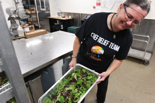 Chef Cheryl Fulton of San Francisco loads a tray of salad onto a cart in an auditorium kitchen on the Chico State University campus on Nov. 22, 2018. Fulton is among volunteers preparing Thanksgiving dinner for evacuees from the Camp Fire in Paradise, Calif.