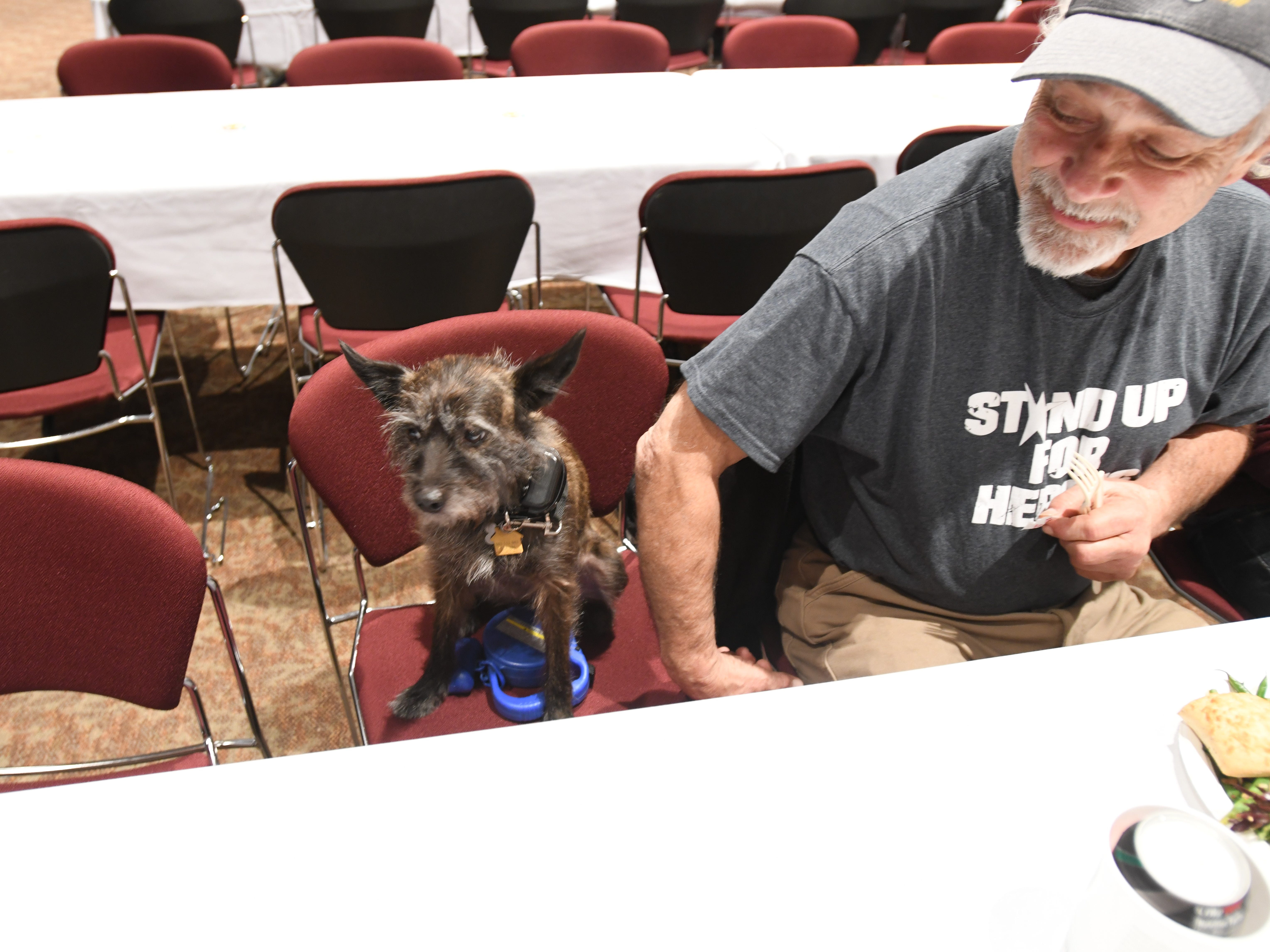 Paul Love and his dog, CocoTwix, enjoy a Thanksgiving meal in an auditorium at Chico State University on Nov. 22, 2018. Love and his wife, Colleen, lost their home in the Camp Fire.