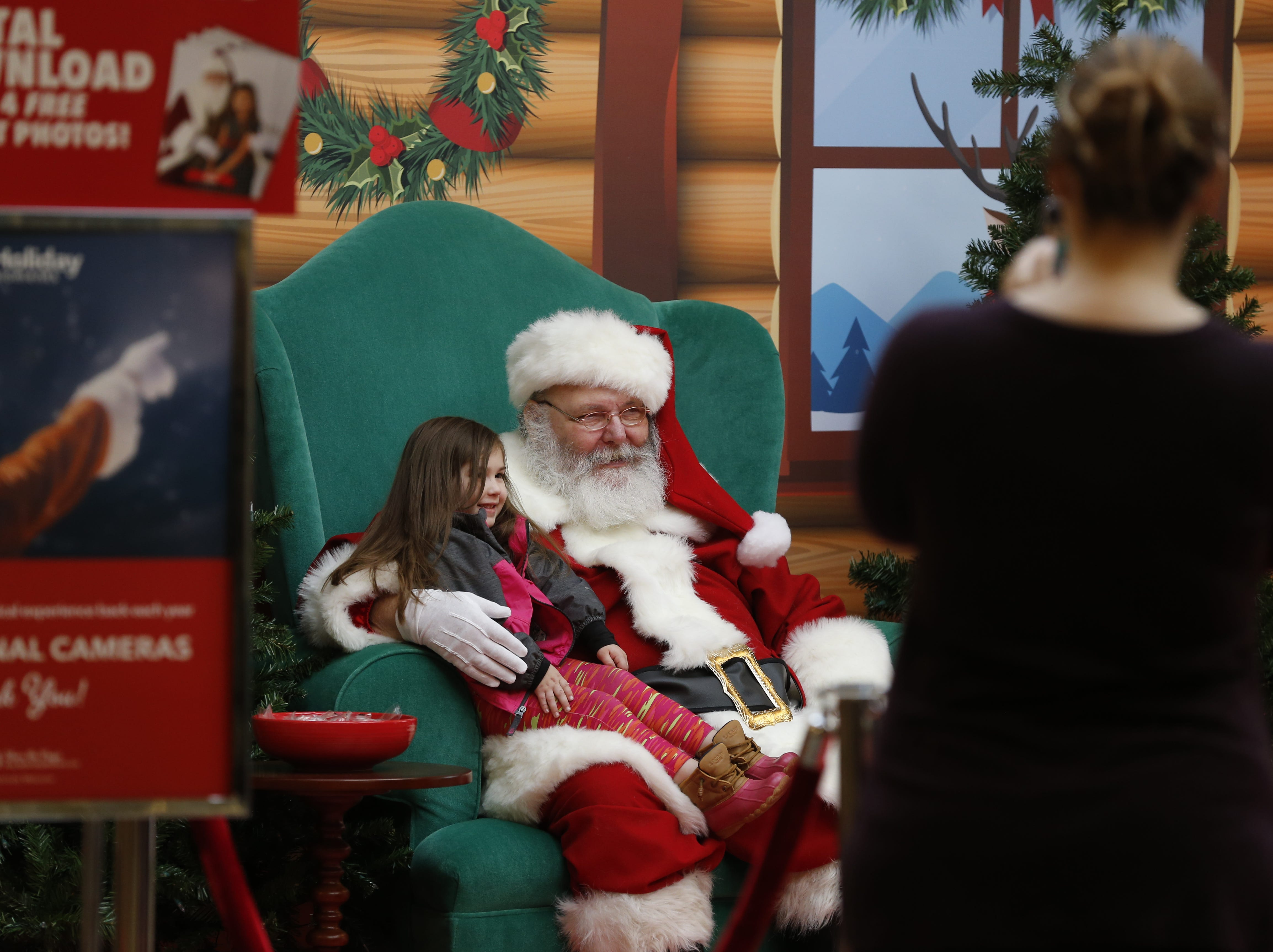 Santa Clause poses with one of the first kids to come see him at the new Santa's Village area at the Richmond Mall on Friday, Nov. 23, 2018.