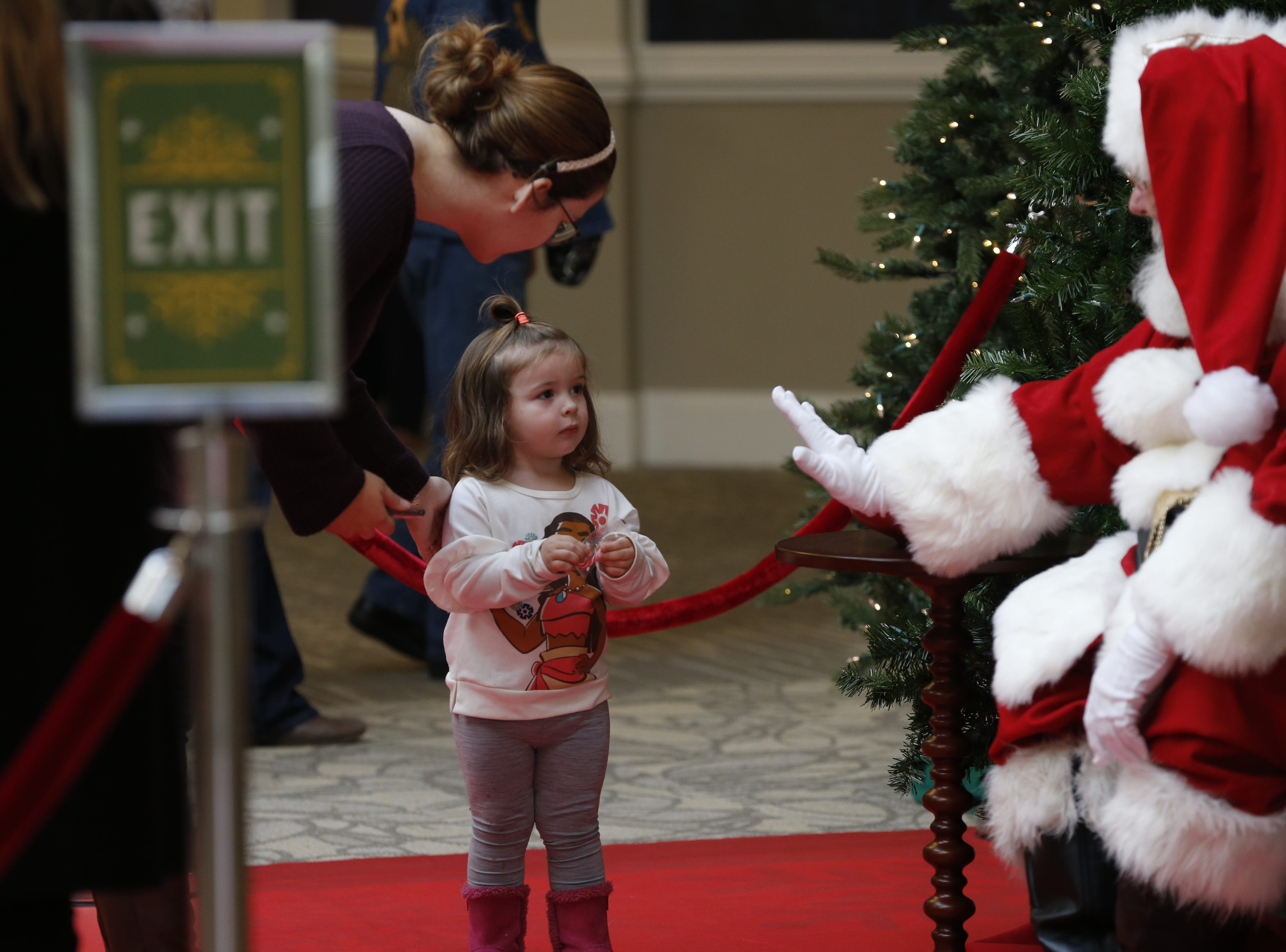 Santa Clause greets one of the first kids to come see him at the new Santa's Village area at the Richmond Mall on Friday, Nov. 23, 2018.