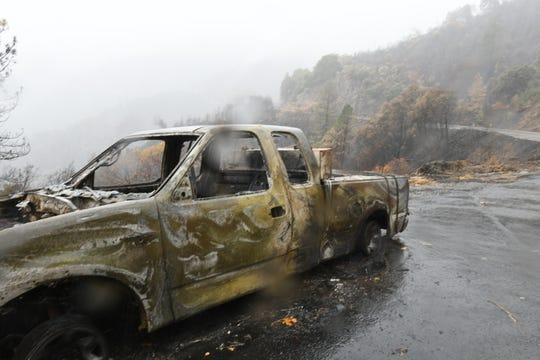 A burned-out truck in steep terrain along Highway 70 near the boundary of Plumas National Forest on Nov. 23, 2018. The stretch of highway is in an area the United States Geological Survey considers at high risk for debris flows due to rain soaking terrain burned in the Camp fire.