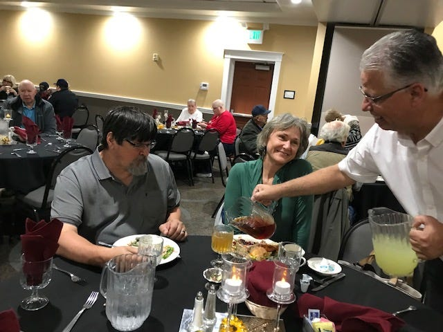 Tony, left, and Kathy Stoltzfus enjoy their Thanksgiving meal at the Holiday Inn Hilltop. Volunteer server Stephan Barnreuther tops off their tea.