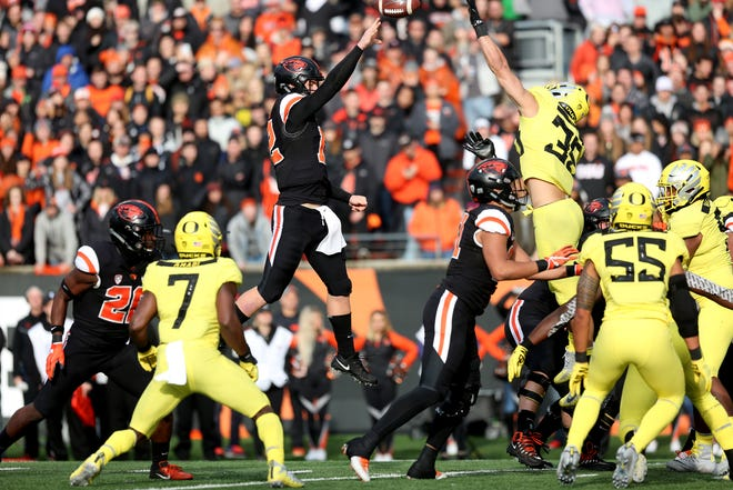 Oregon State's Jack Colletto (12) jumps for a pass past the fingertips of Oregon's Troy Dye (35) in the Oregon vs. Oregon State Civil war football game at Oregon State University in Corvallis on Friday, Nov. 23, 2018. The throw was intercepted by Oregon's Nick Pickett.