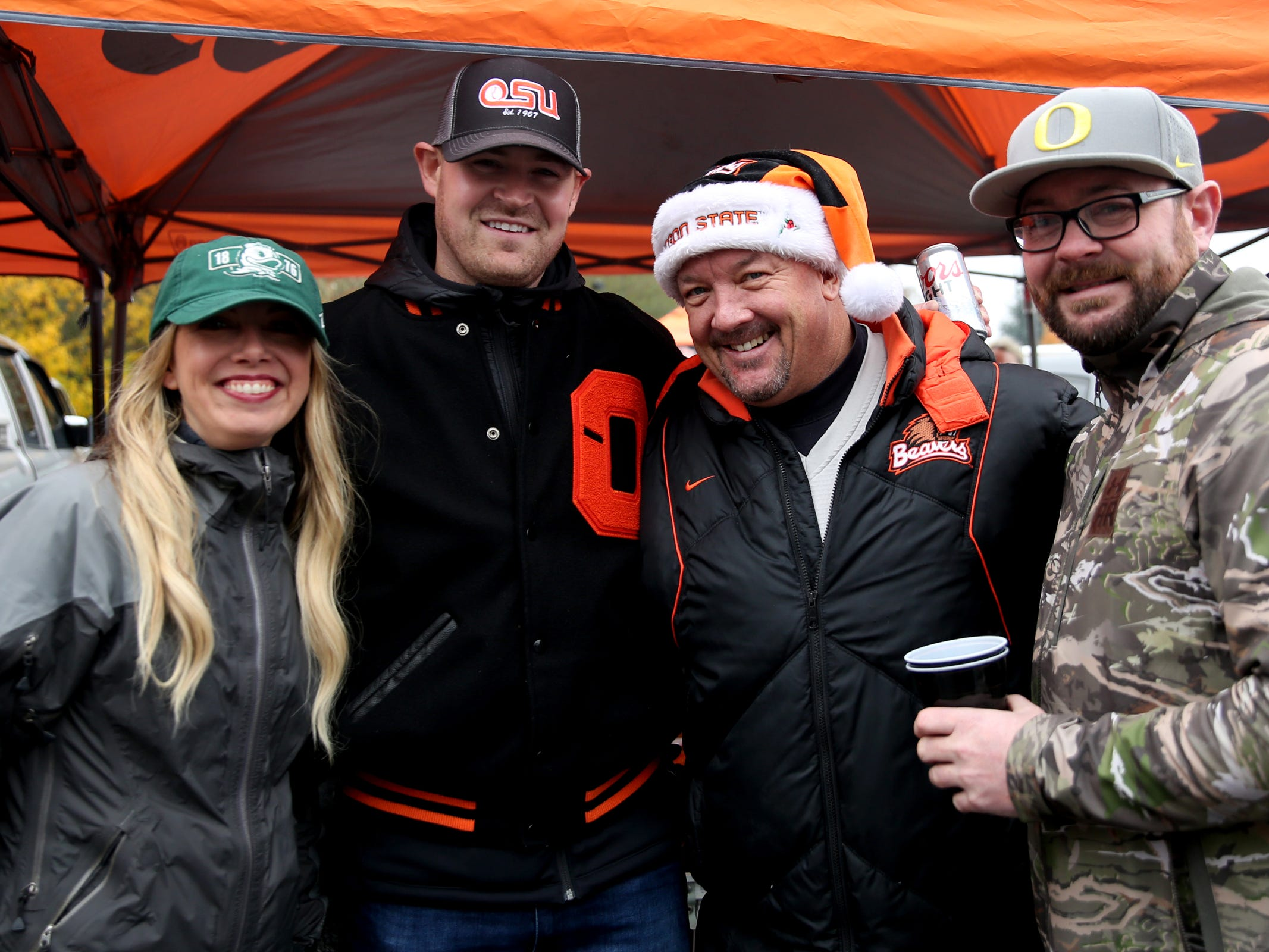 Friends, from left, Lisa Curry, of Portland, Taylor Starr, of Corvallis, Andy Noonan, of Corvallis, and Mark Buckingham, of Portland, root for different teams before the start of the Oregon vs. Oregon State Civil war football game at Oregon State University in Corvallis on Friday, Nov. 23, 2018.