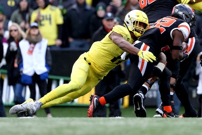 Oregon's Justin Hollins (11) takes down Oregon State's Jermar Jefferson (22) in the Oregon vs. Oregon State football game at Oregon State in Corvallis on Friday, Nov. 23, 2018.