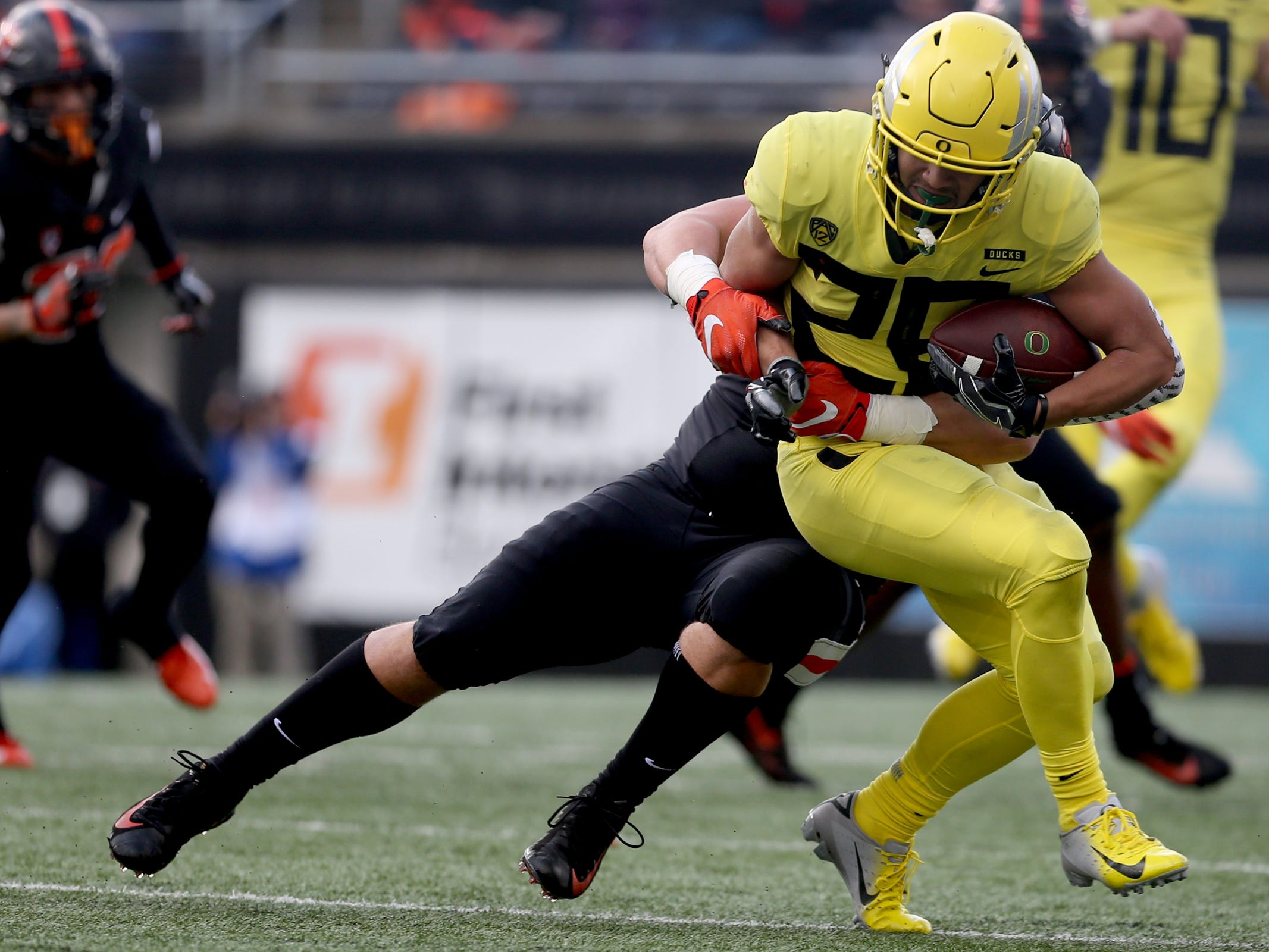 Oregon's Travis Dye (26) is grabbed by Oregon State's Elu Aydon (99) in the Oregon vs. Oregon State Civil war football game at Oregon State University in Corvallis on Friday, Nov. 23, 2018.