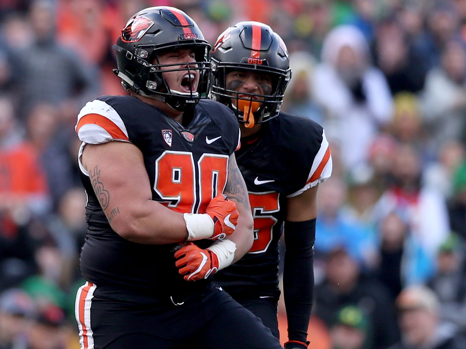 Oregon State's Isaac Hodgins (90) and Jayden Grant (26) celebrate a sack in the Oregon vs. Oregon State Civil war football game at Oregon State University in Corvallis on Friday, Nov. 23, 2018.