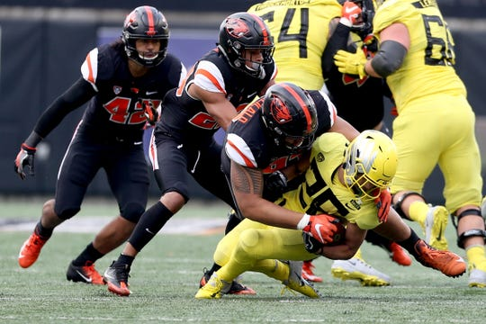 Oregon's Travis Dye (26) is taken down in the Oregon vs. Oregon State Civil war football game at Oregon State University in Corvallis on Friday, Nov. 23, 2018.