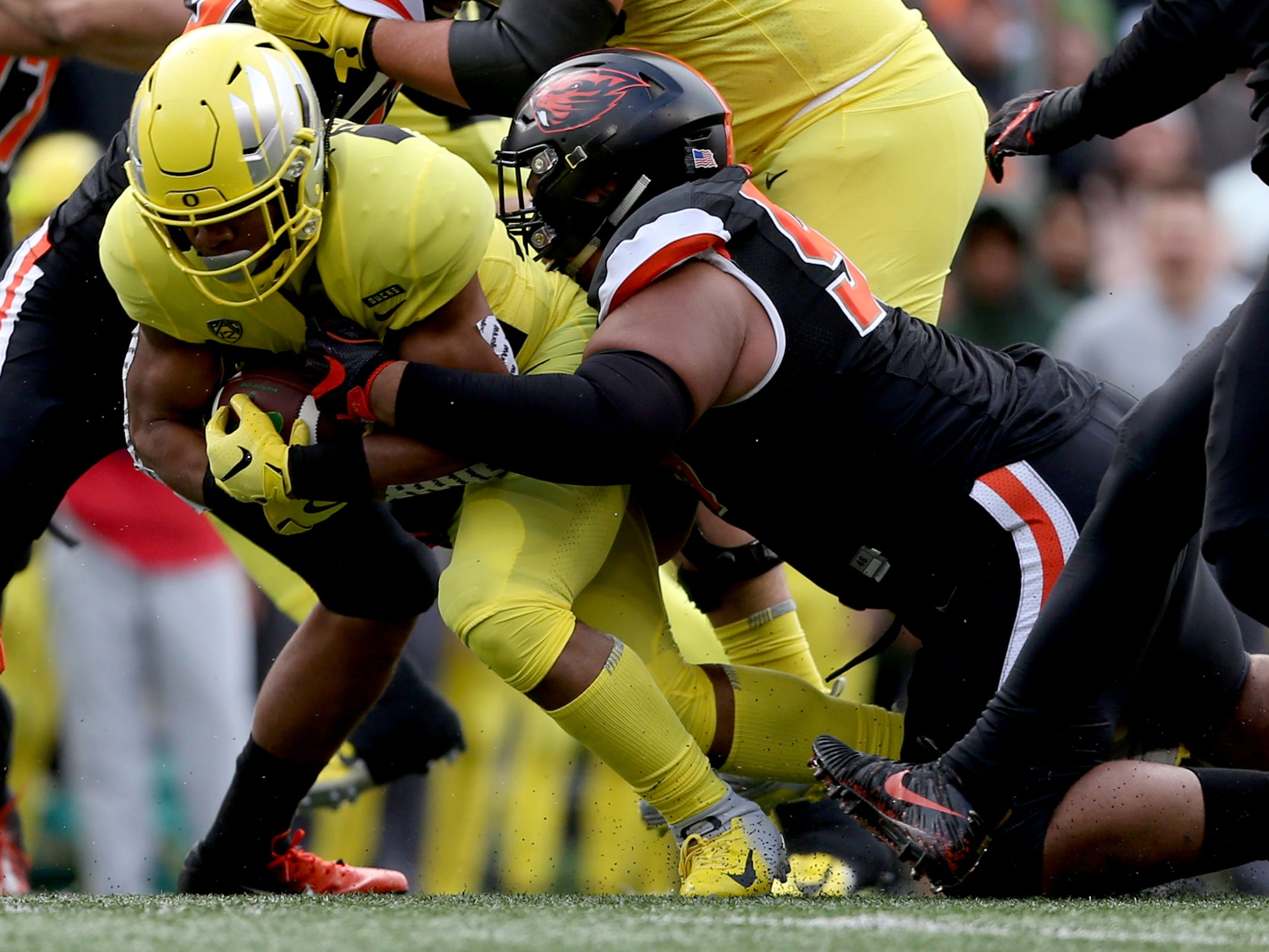 Oregon State's Elu Aydon (99) takes down Oregon's CJ Verdell (34) in the Oregon vs. Oregon State Civil war football game at Oregon State University in Corvallis on Friday, Nov. 23, 2018.