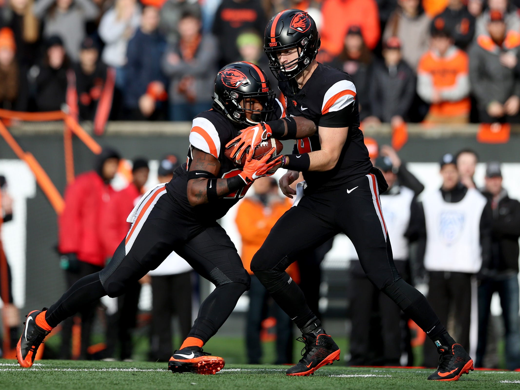 Oregon State's Jake Luton (6) hands the ball off to teammate Jermar Jefferson (22) in the Oregon vs. Oregon State Civil war football game at Oregon State University in Corvallis on Friday, Nov. 23, 2018.
