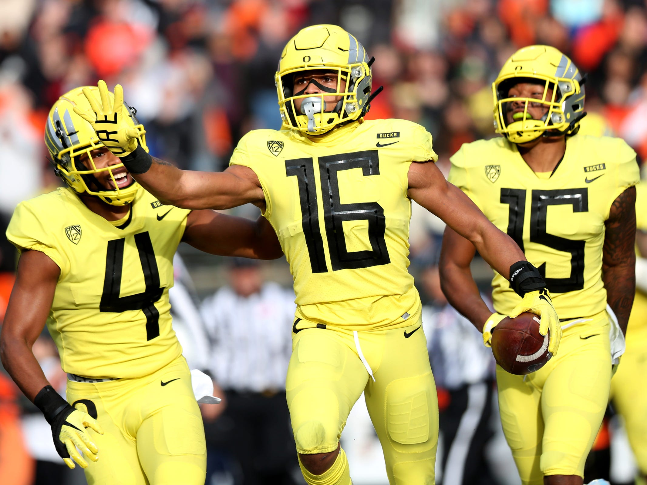 Oregon's Nick Pickett (16), Thomas Graham Jr. (4) and Deommodore Lenoir (15) celebrate an interception by Pickett in the Oregon vs. Oregon State Civil war football game at Oregon State University in Corvallis on Friday, Nov. 23, 2018.