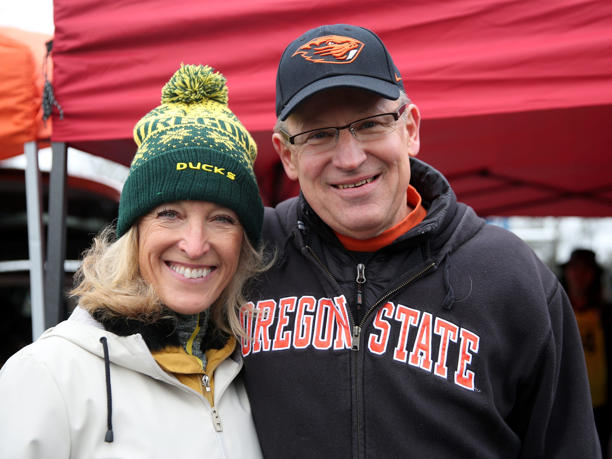 "Pamela and Mike Cook, of Lake Oswego, cheer for different teams before the start of the Oregon vs. Oregon State Civil war football game at Oregon State University in Corvallis on Friday, Nov. 23, 2018. ""This is the only time I get to wear green,"" Pamela said."
