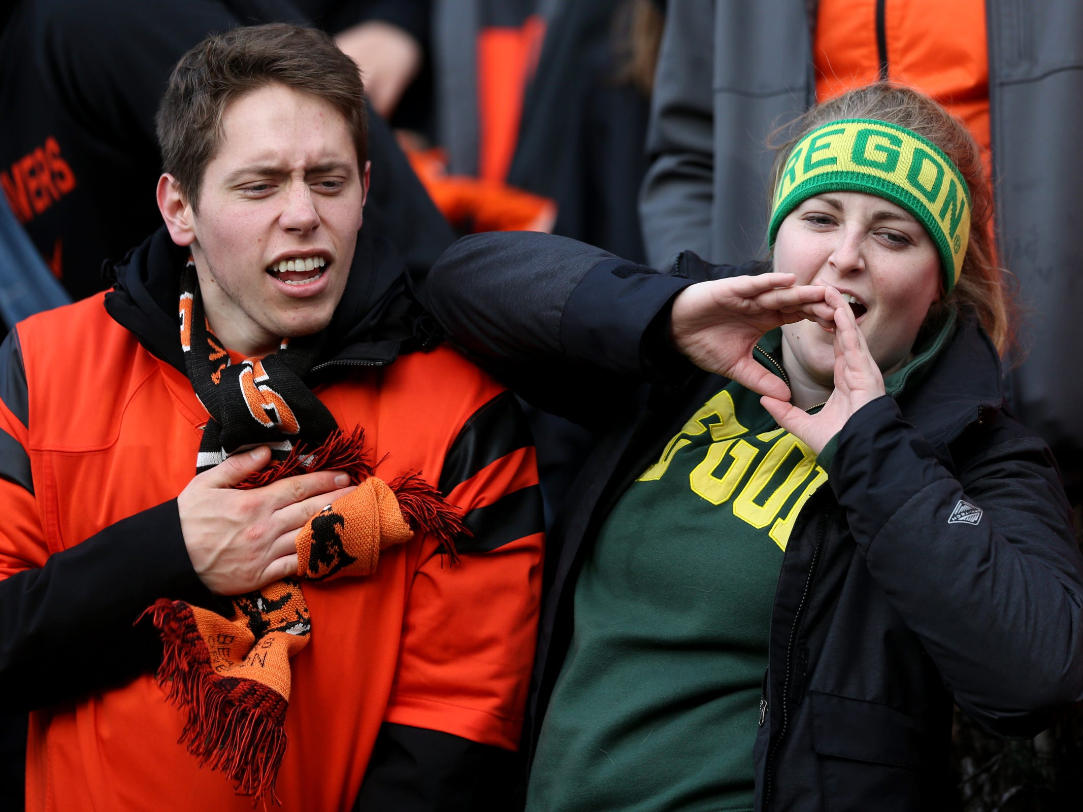 Thomas Cramer, an Oregon State senior math major, and Cari Carter, an Oregon senior human physiology major, cheer on their teams in the Oregon vs. Oregon State Civil war football game at Oregon State University in Corvallis on Friday, Nov. 23, 2018.