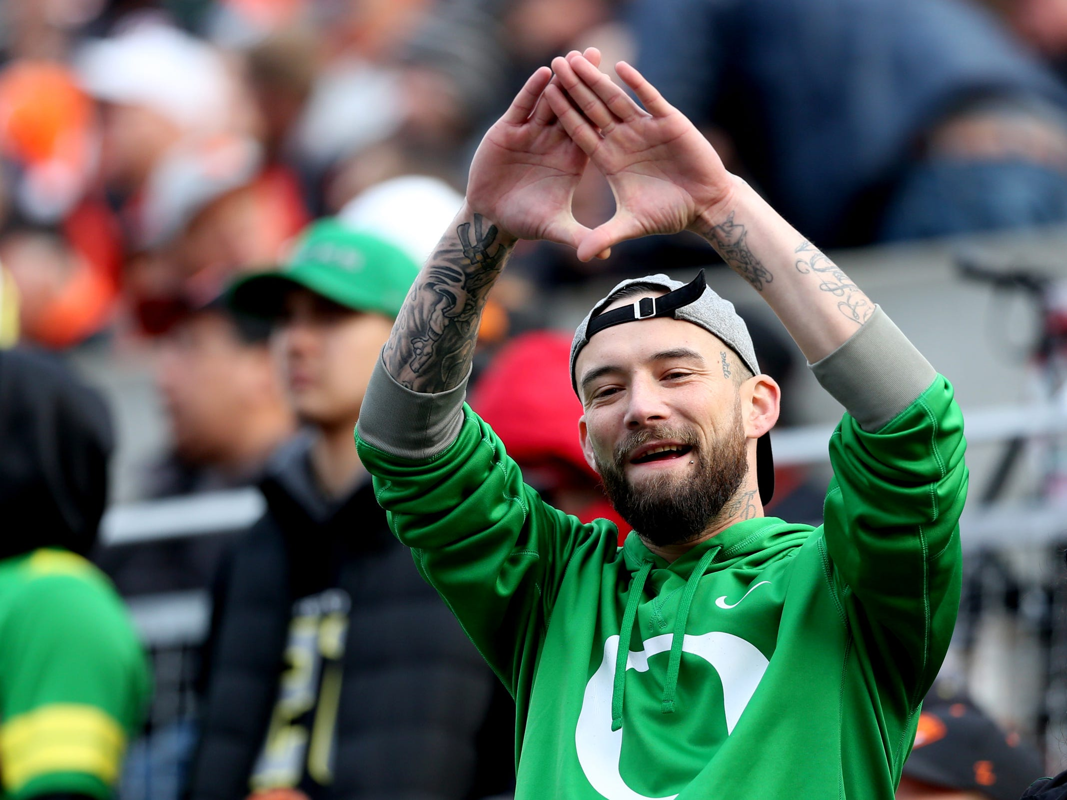 An Oregon fan cheers in the Oregon vs. Oregon State Civil war football game at Oregon State University in Corvallis on Friday, Nov. 23, 2018.