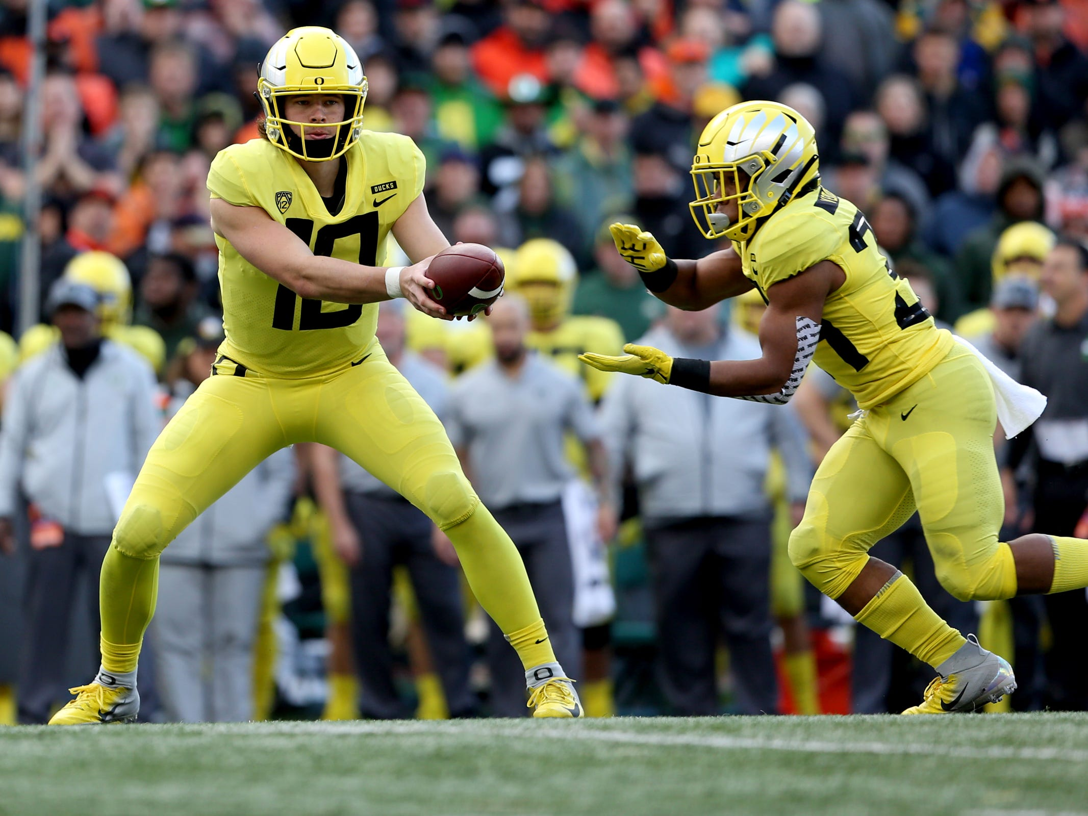Oregon's Justin Herbert (10) hands the ball off to teammate CJ Verdell (34) in the Oregon vs. Oregon State Civil war football game at Oregon State University in Corvallis on Friday, Nov. 23, 2018.