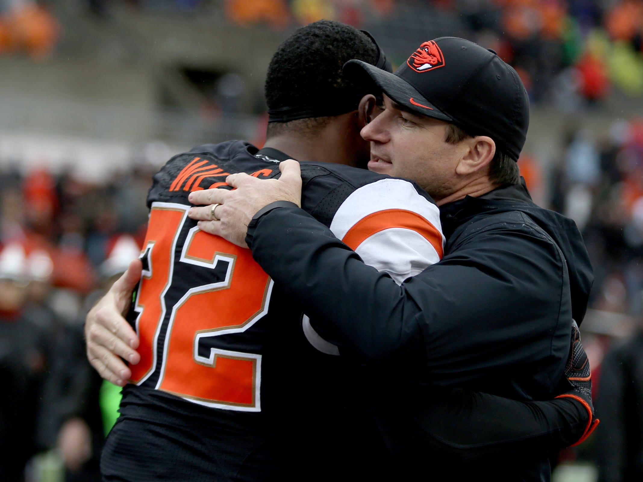 Oregon State head coach Jonathan Smith hugs senior Jonathan Willis (32) before the start of the Oregon vs. Oregon State Civil war football game at Oregon State University in Corvallis on Friday, Nov. 23, 2018.