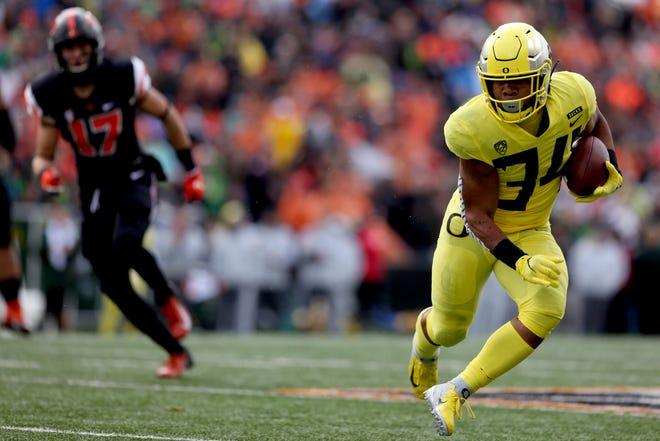 Oregon's CJ Verdell (34) rushes past Oregon State's John McCartan (17) in the Oregon vs. Oregon State Civil war football game at Oregon State University in Corvallis on Friday, Nov. 23, 2018.