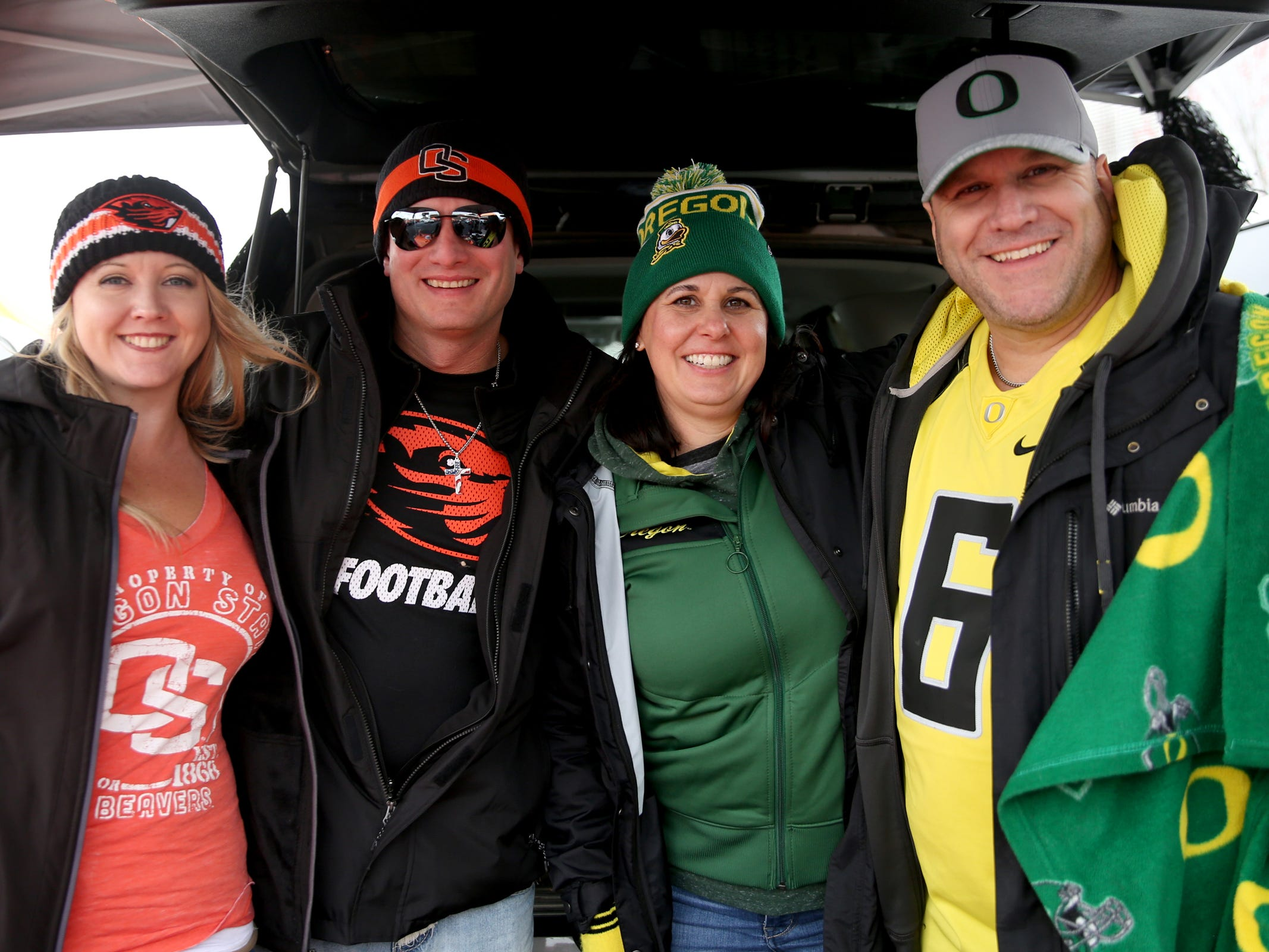 Friends Tanya Williams, from left, Jason Williams, both of Albany, Amy Presley and Chad Presley, both of Forest Grove, root for different teams before the start of the Oregon vs. Oregon State Civil war football game at Oregon State University in Corvallis on Friday, Nov. 23, 2018.