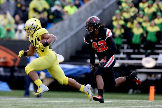 Oregon's CJ Verdell (34) rushes past Oregon State's Doug Taumoelau (42) in the Oregon vs. Oregon State Civil war football game at Oregon State University in Corvallis on Friday, Nov. 23, 2018.