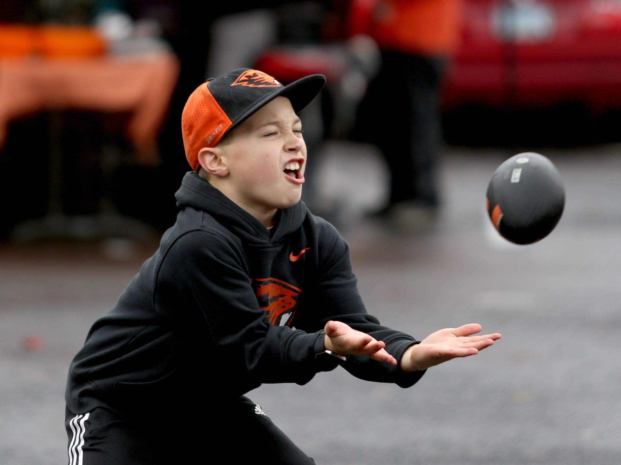 Derek Davis, 9, of Corvallis, plays catch before the start of the Oregon vs. Oregon State Civil war football game at Oregon State University in Corvallis on Friday, Nov. 23, 2018.
