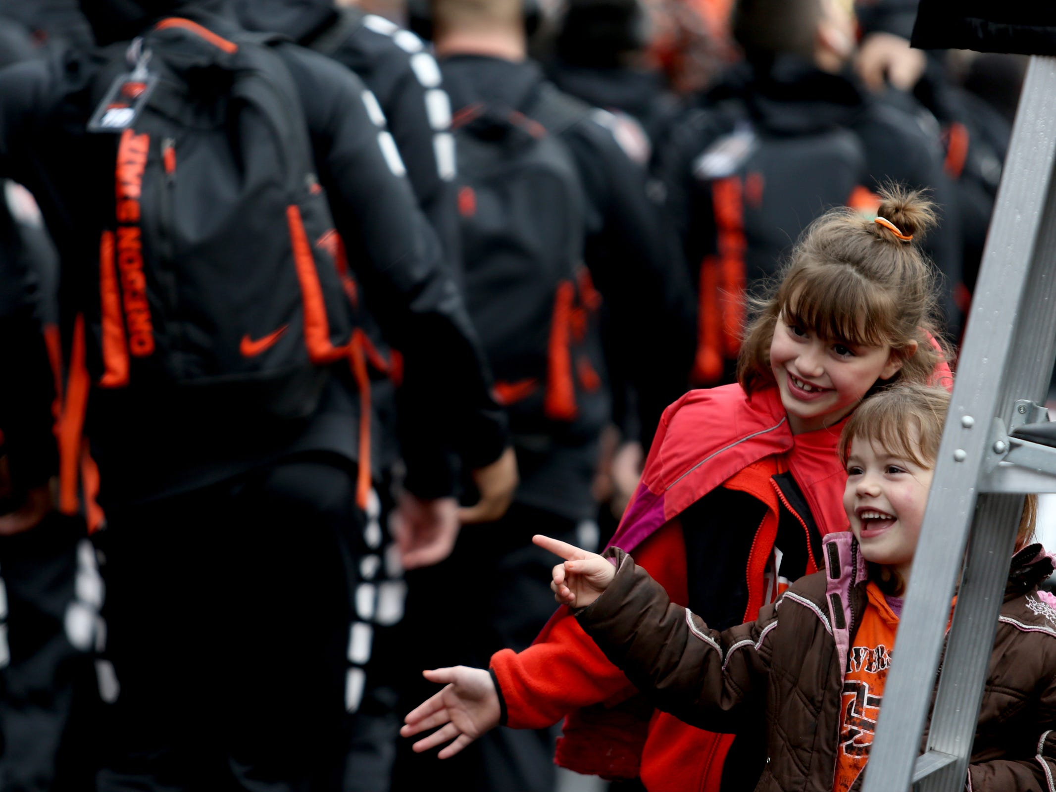 Sisters Kayla, 9, and Kaitlyn Russio, 6, of Happy Valley, wave to Oregon State players before the start of the Oregon vs. Oregon State Civil war football game at Oregon State University in Corvallis on Friday, Nov. 23, 2018.